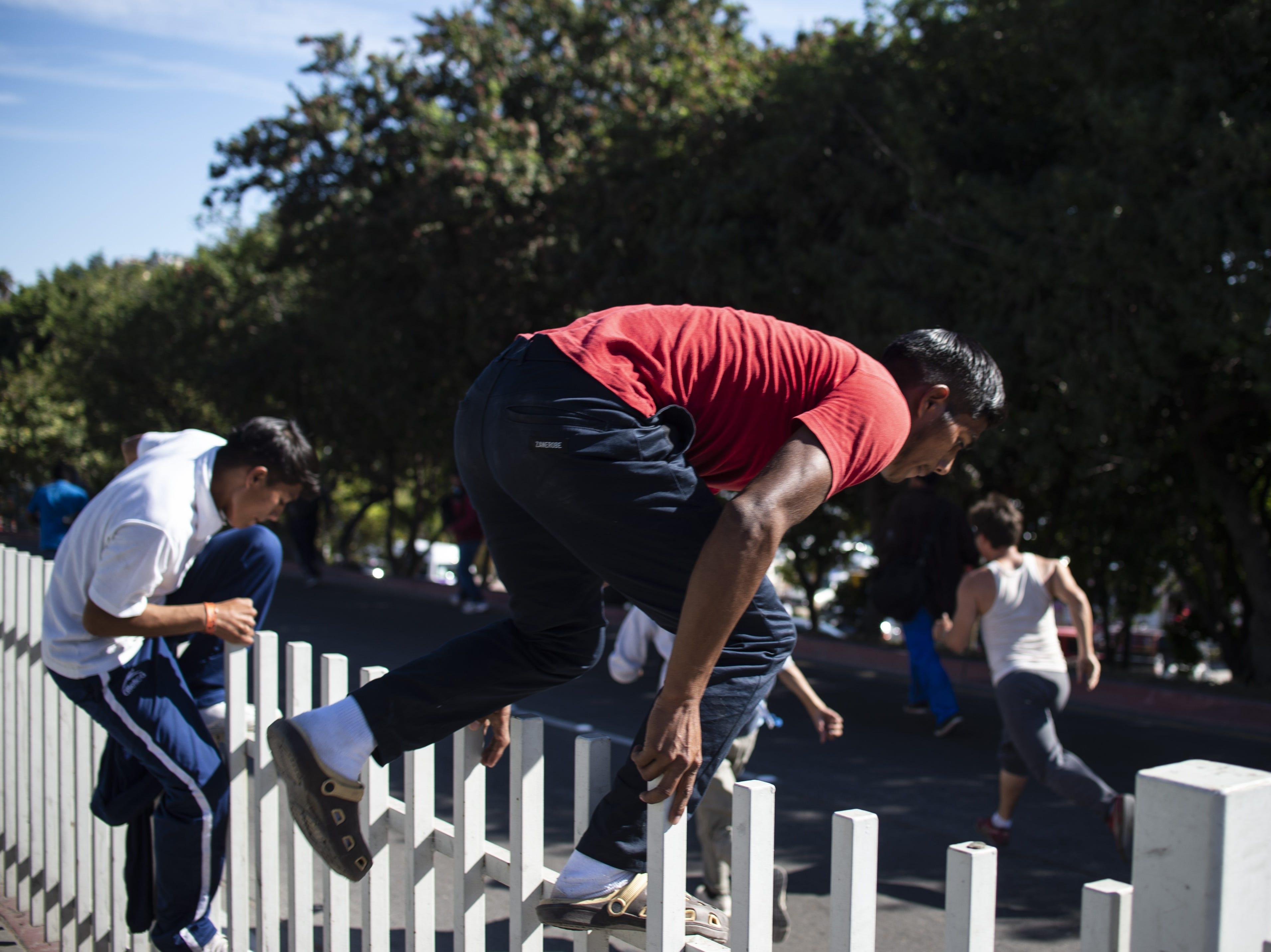 Un grupo de migrantes centroamericanos, en su mayoría hondureños, sobrepasa una cerca al intentar llegar a la frontera entre México y Estados Unidos cerca del cruce fronterizo de El Chaparral en Tijuana, estado de Baja California, México, el 25 de noviembre de 2018.