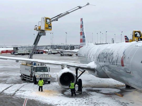 El lunes 26 de noviembre de 2018, en Chicago, las tripulaciones eliminan el hielo de un avión de American Airlines en el Aeropuerto Internacional O'Hare. Una tempestad invernal trajo condiciones de tormenta de nieve a partes del Medio Oeste el lunes temprano, aterrizando cientos de vuelos y causando carreteras resbaladizas para los pasajeros que regresaban al trabajo después del fin de semana de Acción de Gracias.