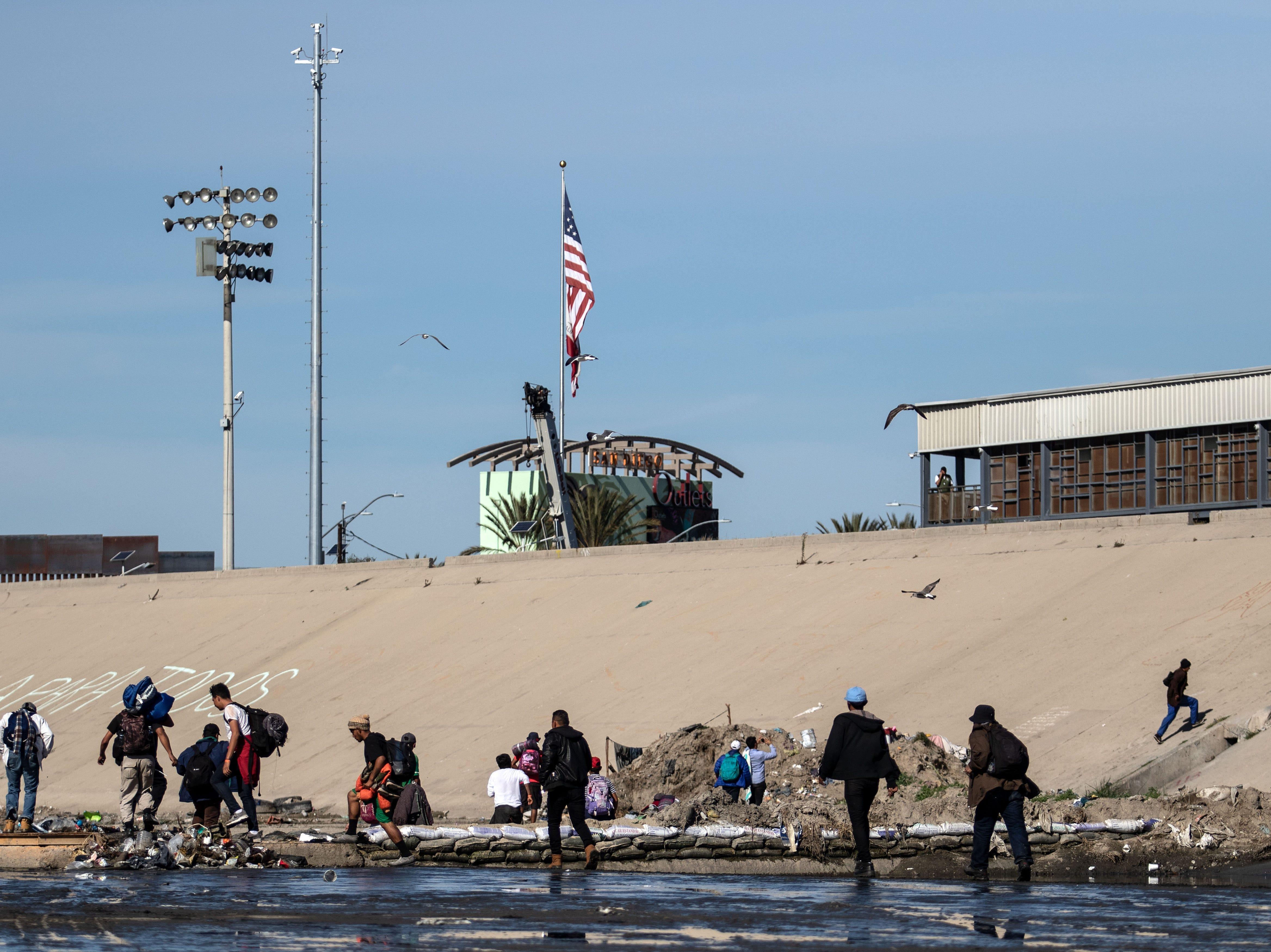 Los migrantes centroamericanos, principalmente de Honduras, cruzan la vía de agua poco profunda del río Tijuana en su intento ppor llegar al punto fronterizo de El Chaparral en Tijuana, estado de Baja California, México, el 25 de noviembre de 2018.