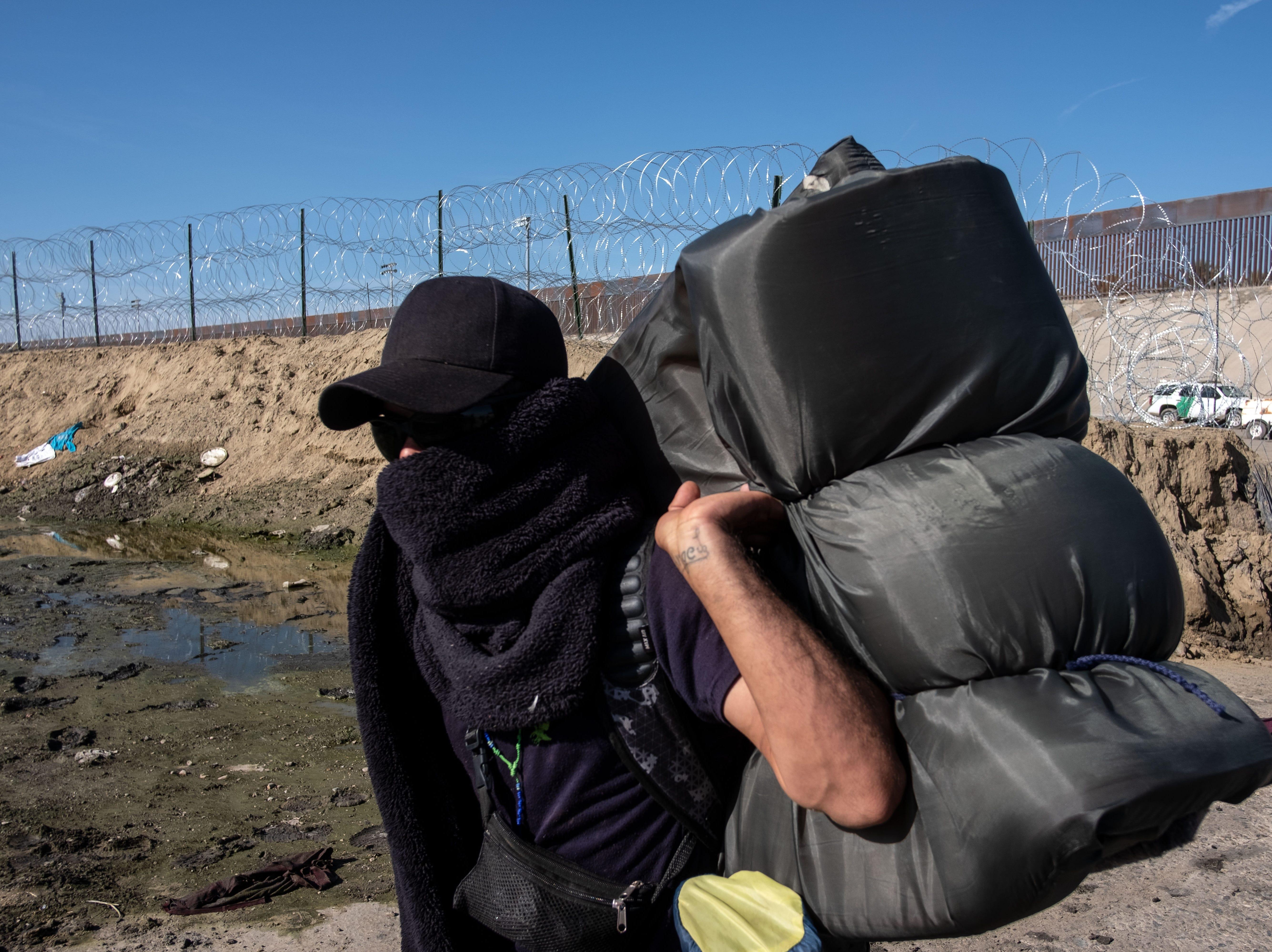 Un hombre que viaja con una caravana de migrantes centroamericanos, principalmente de Honduras, con la esperanza de llegar a los Estados Unidos, camina cerca de una barricada establecida por la Patrulla Fronteriza de los EE.UU a lo largo del río Tijuana, cerca del cruce fronterizo de El Chaparral en Tijuana, Baja California. Estado, México, el 25 de noviembre de 2018.