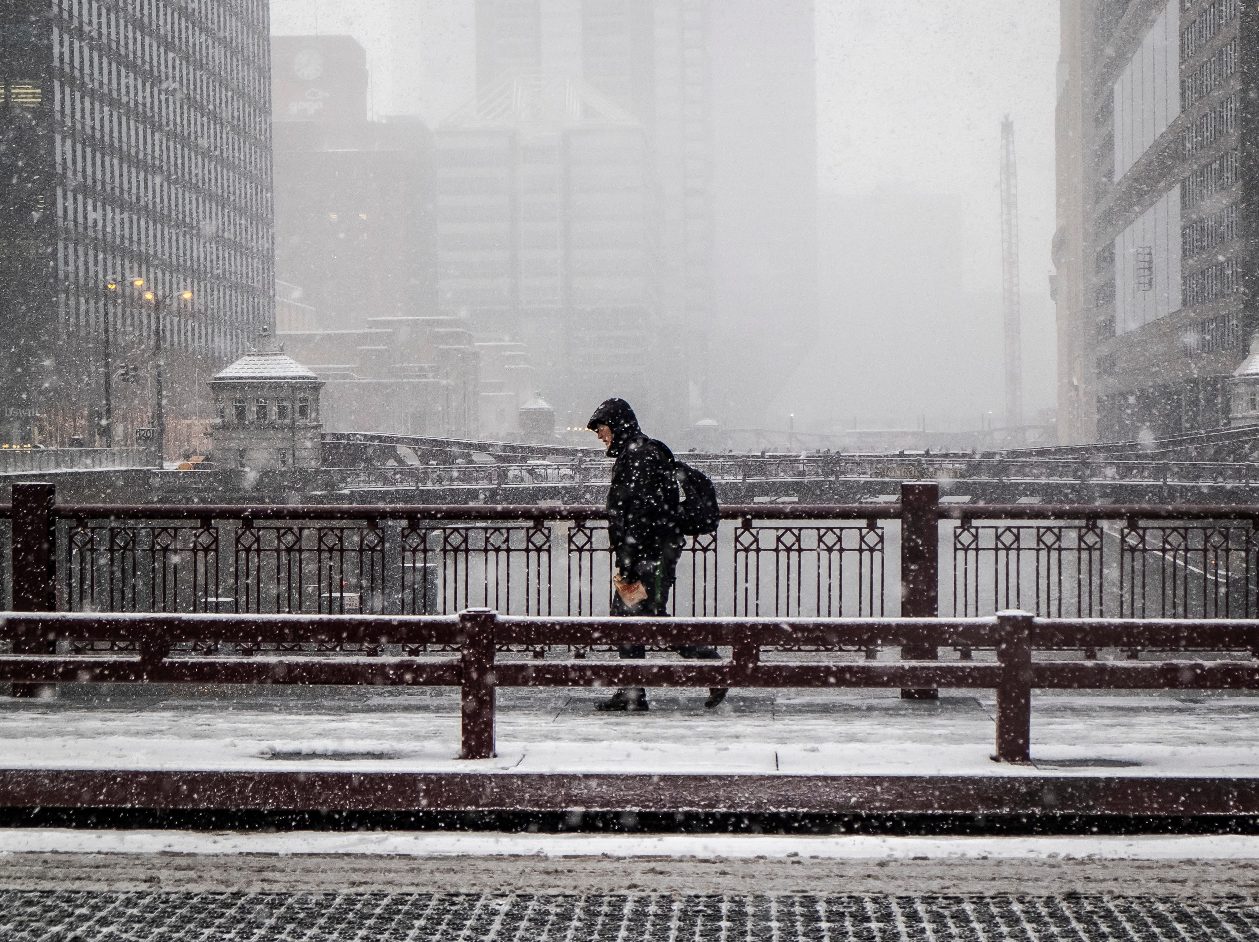 Un residente cruzan el río Chicago en la calle Adams, en Chicago el 26 de noviembre de 2018. Una tempestad invernal trajo condiciones de tormenta de nieve a partes del Medio Oeste el lunes temprano, aterrizando cientos de vuelos y causando un caos en el tráfico mientras los viajeros regresaban al trabajo después del fin de semana de Acción de Gracias.