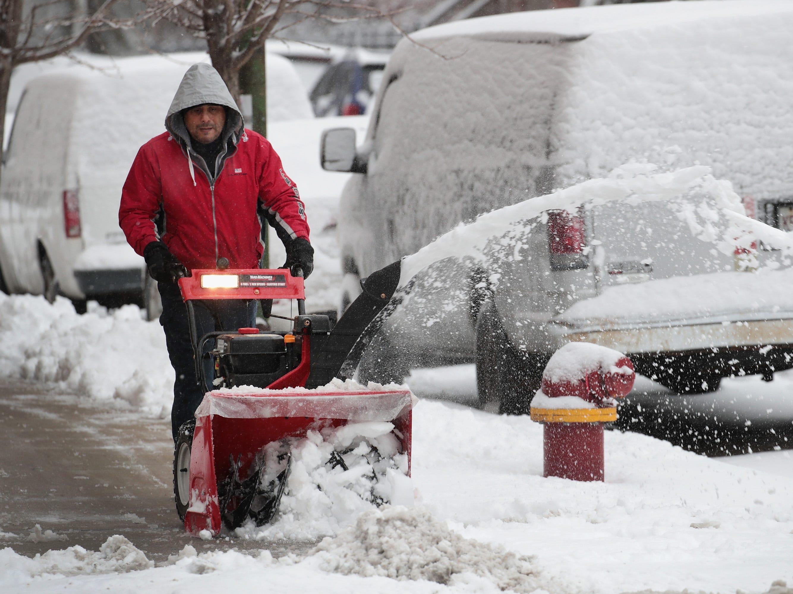 Los residentes de Humboldt Park quitan la nieve después de una tormenta que arrojó varias pulgadas de nieve en el vecindario el 26 de noviembre de 2018 en Chicago, Illinois. La tormenta, que comenzó el domingo por la mañana con la lluvia convirtiéndose en nieve, se elevó a un pie en Chicago y sus alrededores.