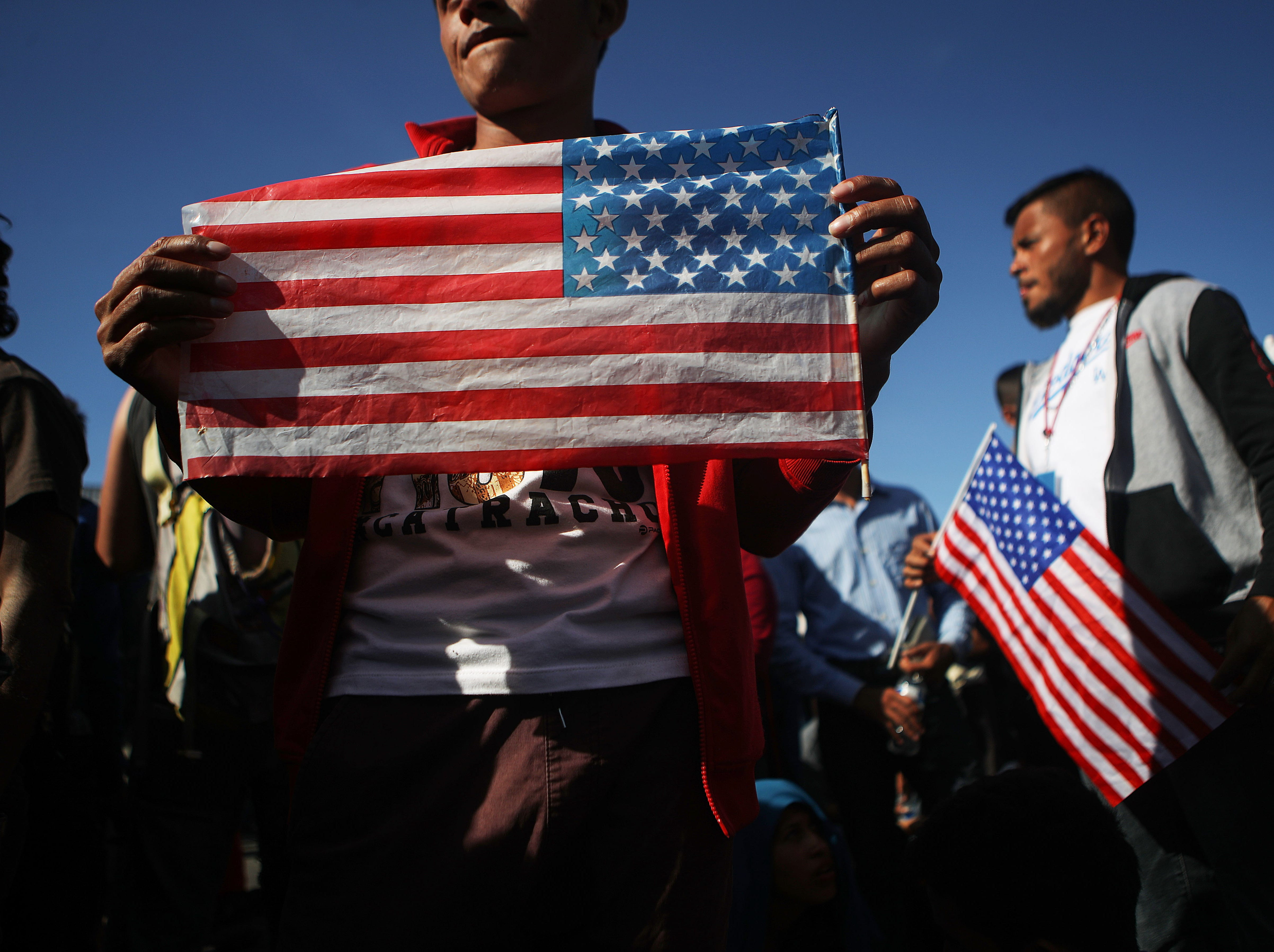 Los migrantes sostienen banderas estadounidenses durante una marcha pacífica poco antes de que algunos evadieran un bloqueo policial y se apresuraran hacia el puerto de entrada de El Chaparral el 25 de noviembre de 2018 en Tijuana, México.