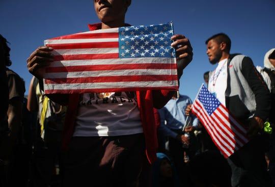 Migrantes sostienen en sus manos banderas de Estados Unidos.