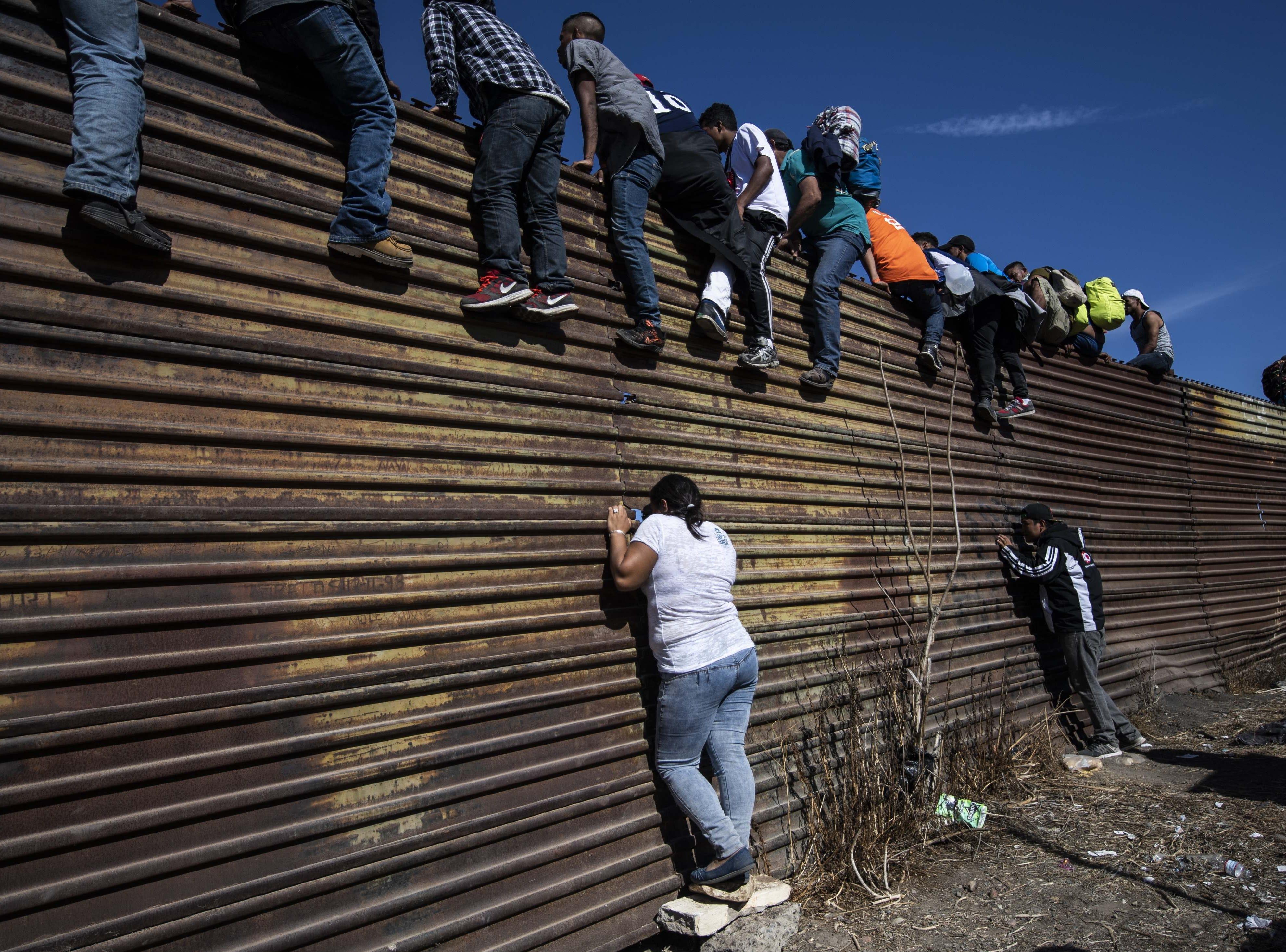Un grupo de migrantes centroamericanos, en su mayoría hondureños, escalan una barrera de metal en la frontera entre México y EE.UU. cerca del cruce fronterizo de El Chaparral, en Tijuana, estado de Baja California, México, el 25 de noviembre de 2018.