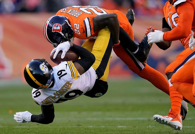 Pittsburgh Steelers wide receiver JuJu Smith-Schuster (19) is hit by Denver Broncos defensive back Tramaine Brock (22) during the first half of an NFL football game, Sunday, Nov. 25, 2018, in Denver. (AP Photo/Jack Dempsey)
