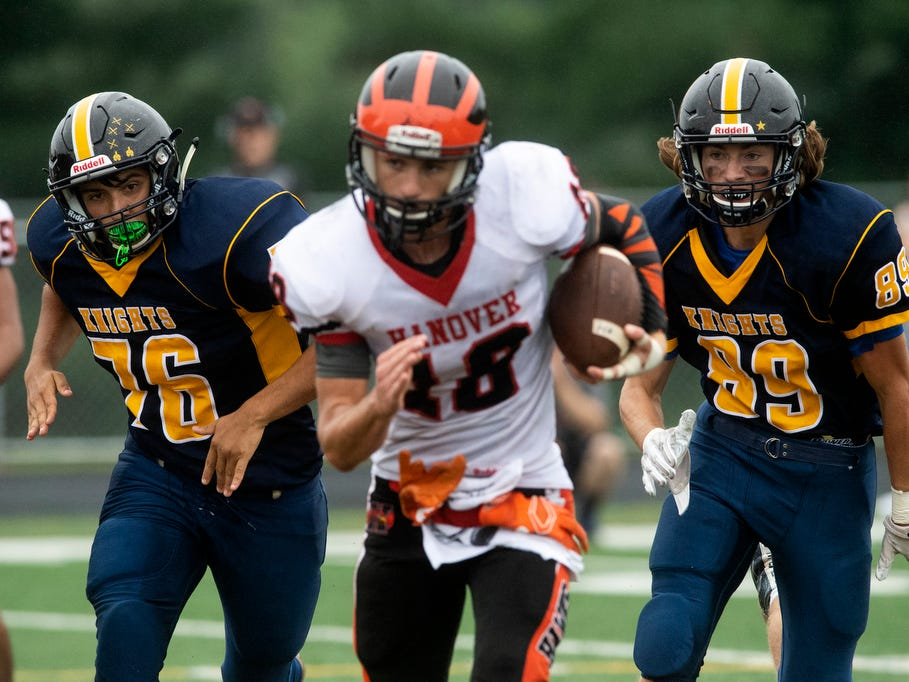 Eastern York's Jared Elamri (76) and Nate Barnhart (89) chase down Hanover quarterback Sam Duvall (18), Saturday, September 1, 2018. The Eastern York Golden Knights (2-0) beat the Hanover Nighthawks (0-2) 47-21, at Eastern York High School.