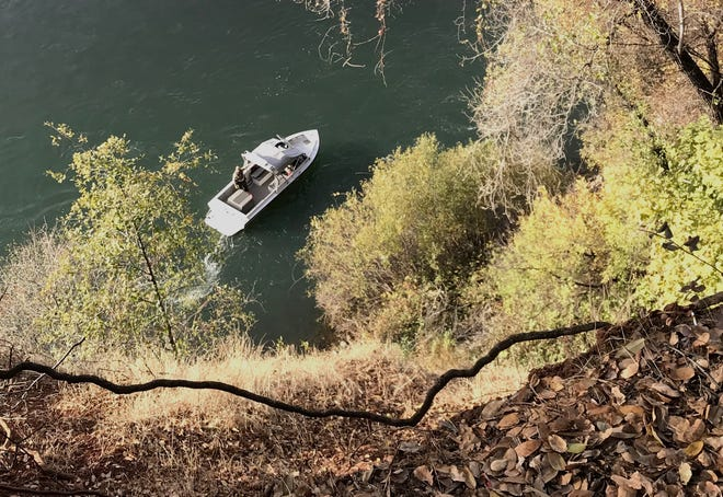 Shasta County sheriff's boating safety team looks for a person that reportedly fell off a nearby cliff on the banks of the Sacramento River in the area off north Bechelli Lane on Sunday.