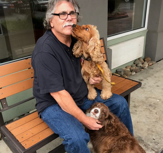 John Gillander, whose Paradise home was destroyed in the Camp Fire, relaxes Monday outside a  Redding motel with his two dogs, Charlie-Horse and Scarlett.