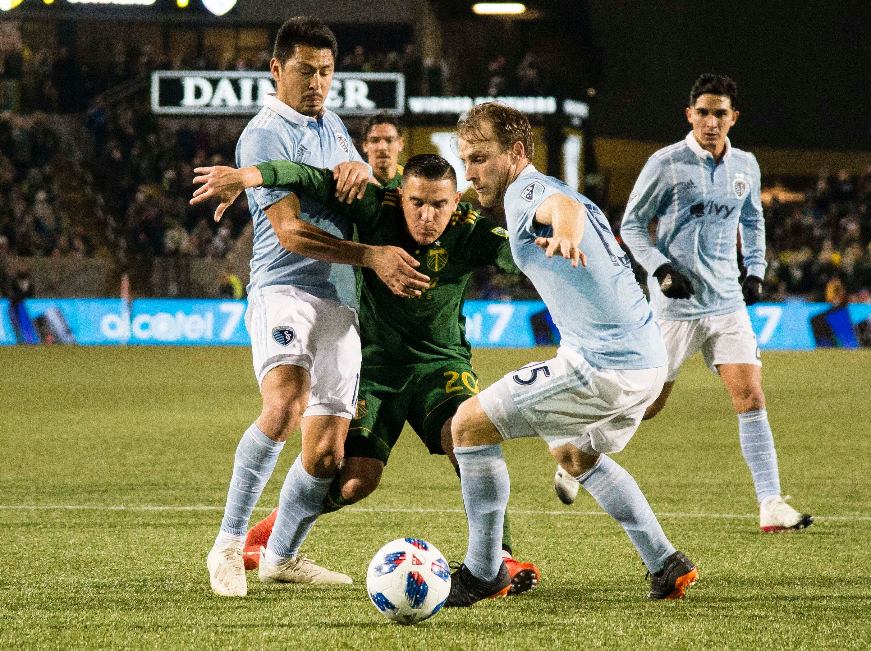 Sporting Kansas City midfielder Roger Espinoza (17) and defender Seth Sinovic (15) stop Portland Timbers midfielder David Guzman (20) during the first half in the first leg of the MLS Western Conference Championship at Providence Park.
