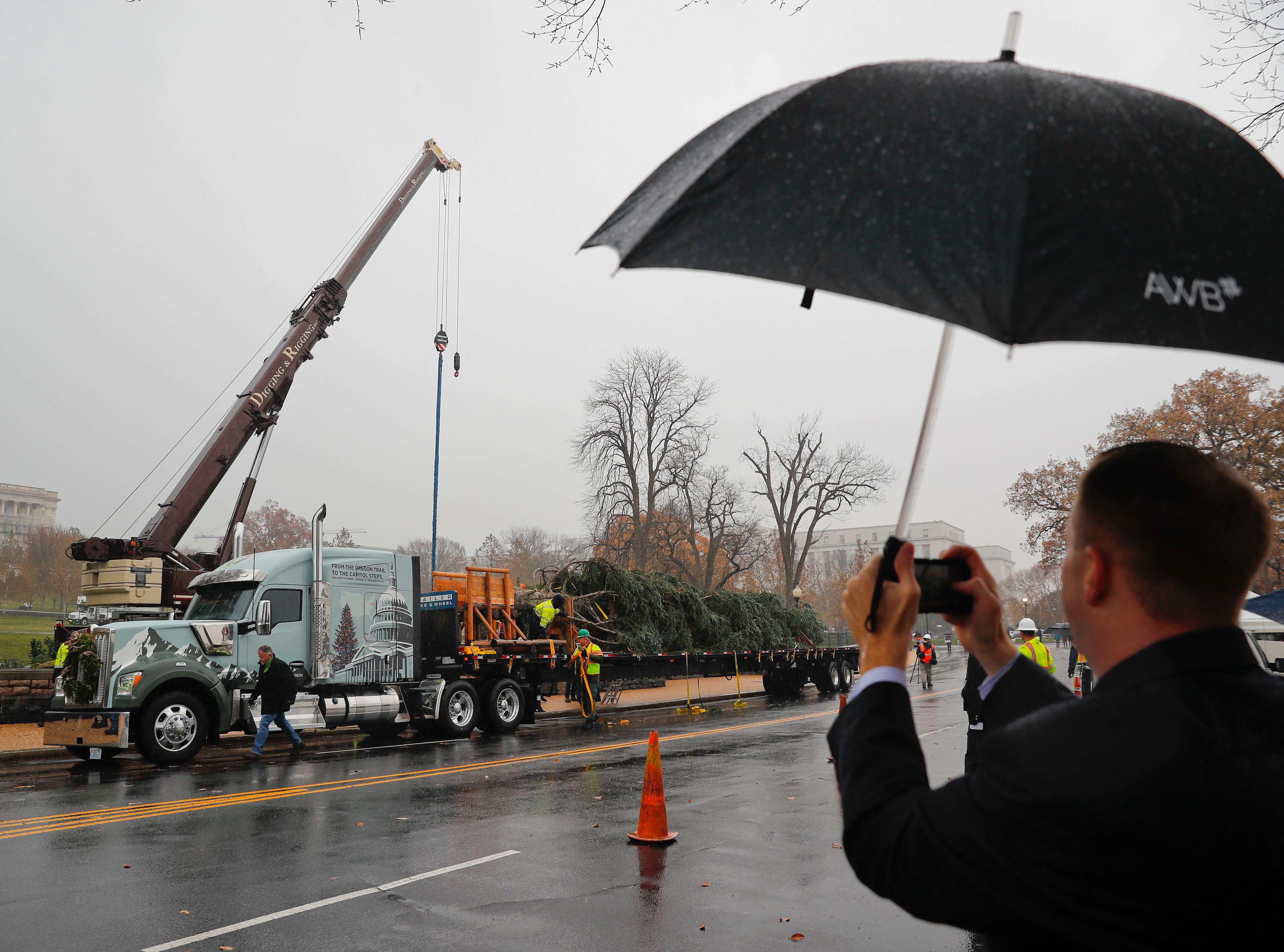 A man takes a picture of the arrival of the 2018 U.S. Capitol Christmas Tree to the West Lawn of the U.S. Capitol Building in Washington, Monday, Nov. 26, 2018, from Willamette National Forest in Oregon.