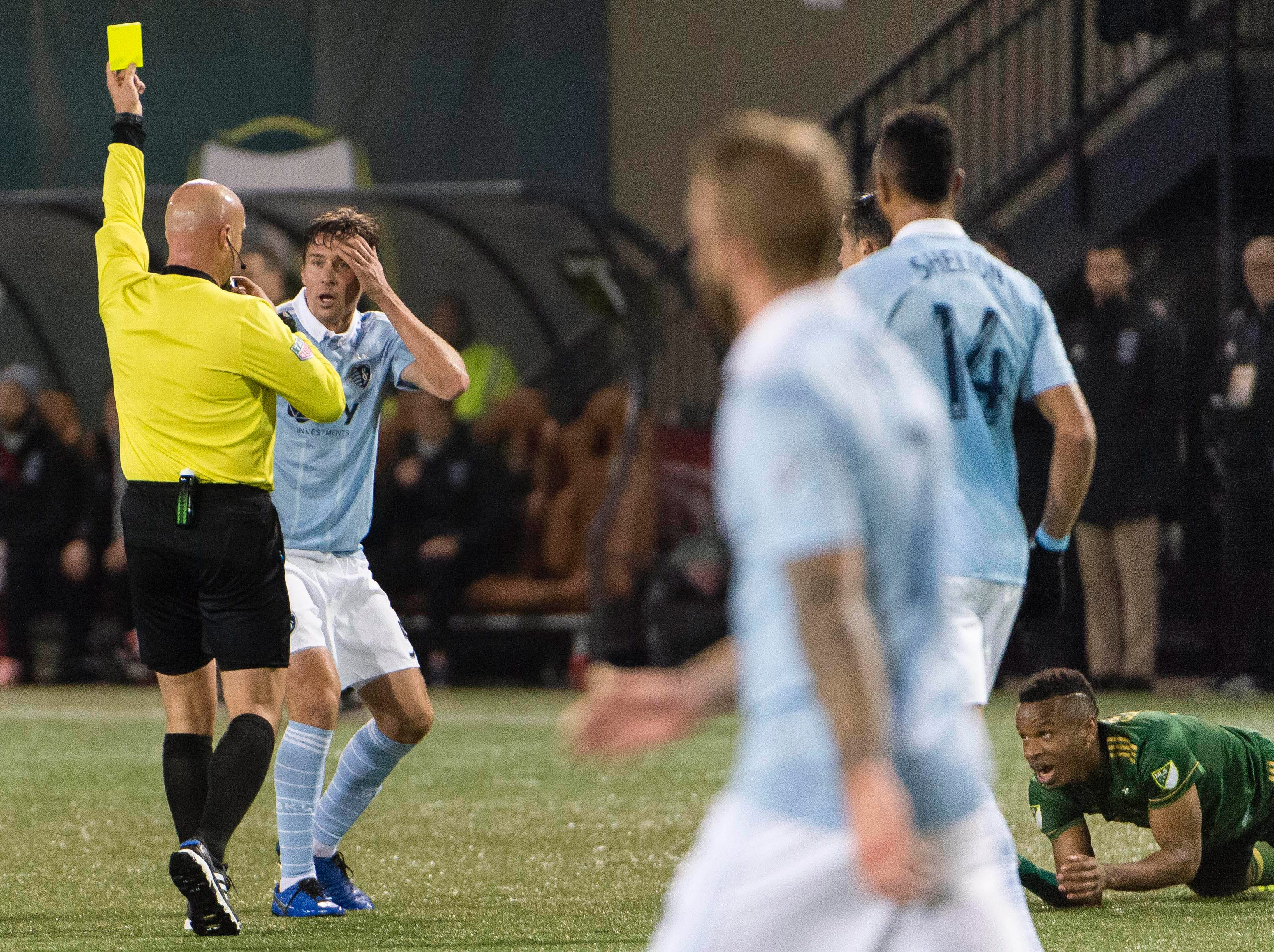 Nov 25, 2018; Portland, OR, USA; Sporting Kansas City defender Matt Besler (5) is given a yellow card during the second half after fouling Portland Timbers forward Jeremy Ebobisse (17) in the first leg of the MLS Western Conference Championship at Providence Park. The game ended tied 0-0. Mandatory Credit: Troy Wayrynen-USA TODAY Sports