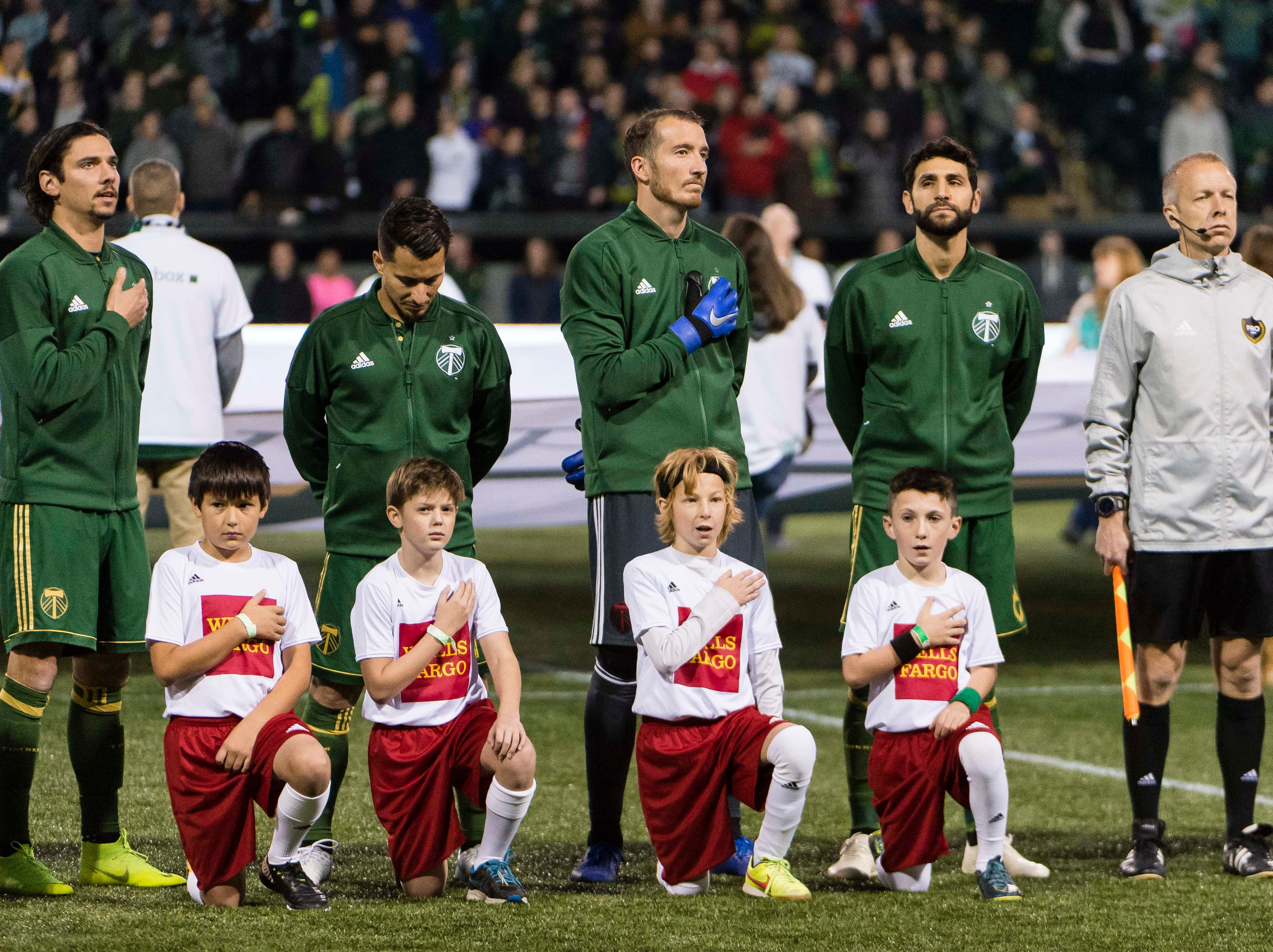 Nov 25, 2018; Portland, OR, USA; The Portland Timbers stand during the playing of the National Anthem before a game against Sporting Kansas City in the first leg of the MLS Western Conference Championship at Providence Park. The game ended tied 0-0.  Mandatory Credit: Troy Wayrynen-USA TODAY Sports