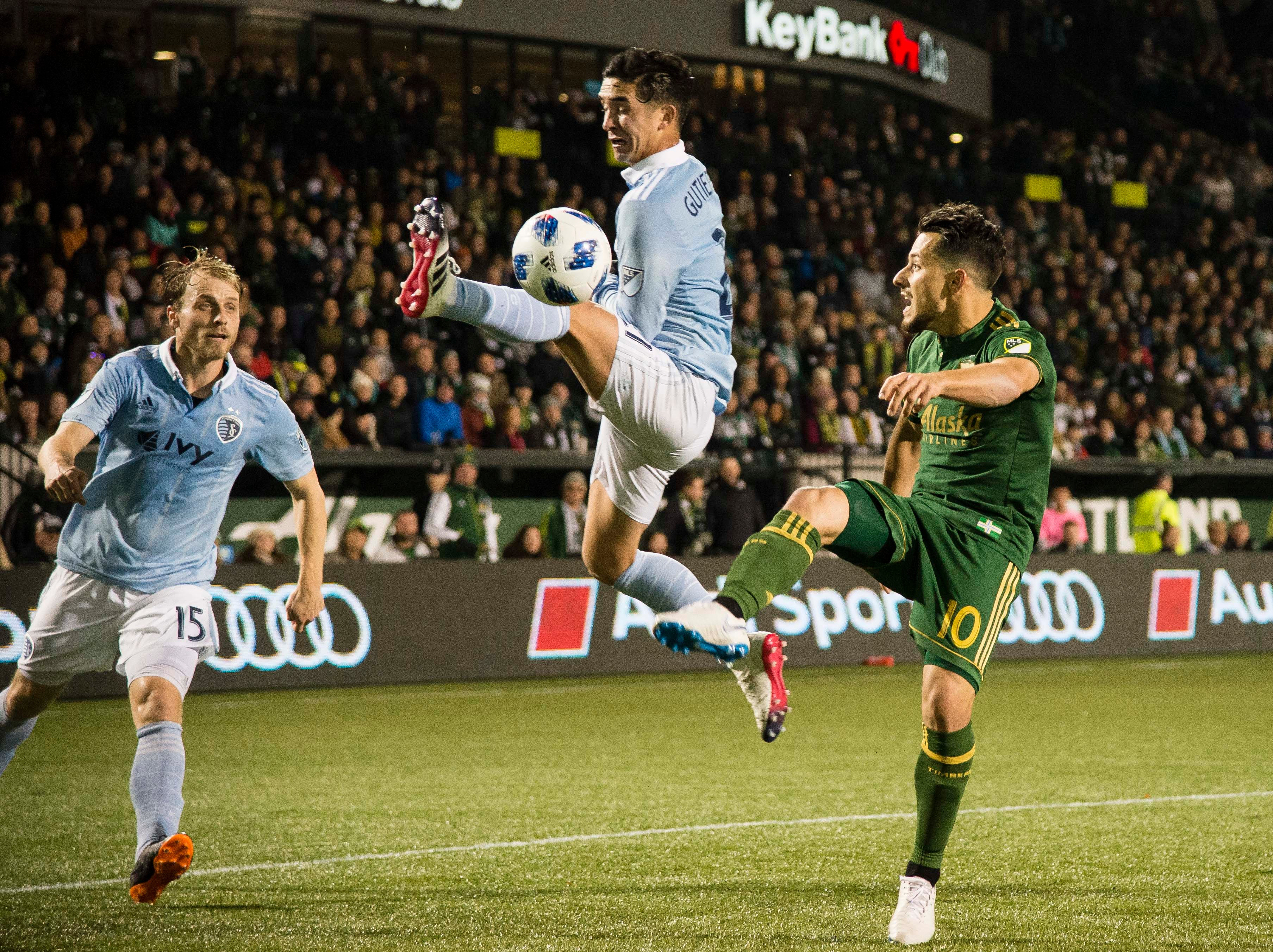 Sporting Kansas City midfielder Felipe Gutierrez (21) kicks the ball away from Portland Timbers midfielder Sebastian Blanco (10) during the first half in the first leg of the MLS Western Conference Championship at Providence Park.