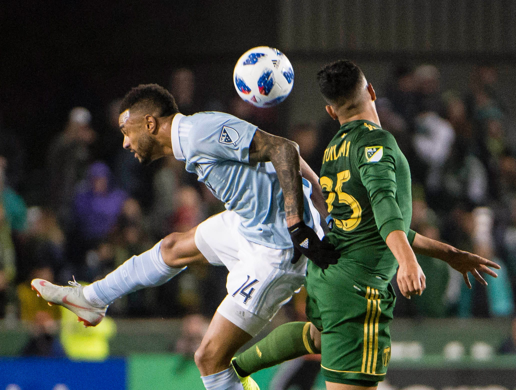 Nov 25, 2018; Portland, OR, USA; Sporting Kansas City forward Khiry Shelton (14) and Portland Timbers defender Bill Tuiloma (25) battle for a header during the second half in the first leg of the MLS Western Conference Championship at Providence Park. The game ended tied 0-0.  Mandatory Credit: Troy Wayrynen-USA TODAY Sports