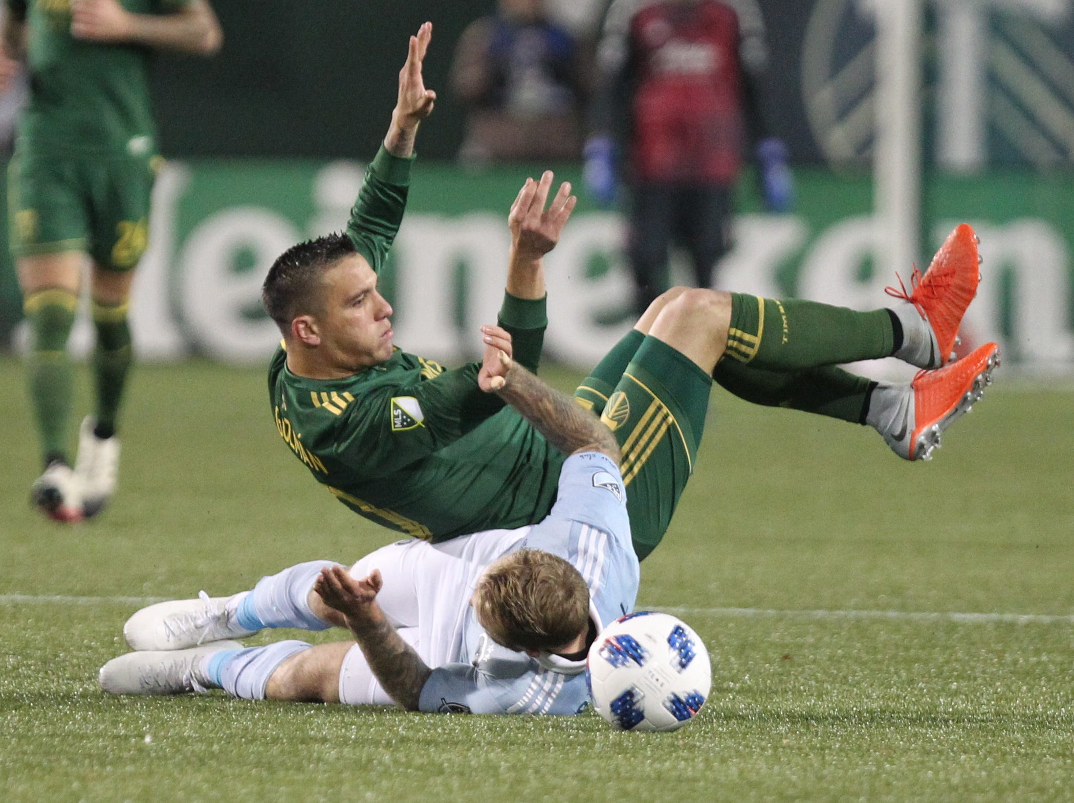 Nov 25, 2018; Portland, OR, USA; Portland Timbers midfielder David Guzman (20) rolls over Sporting Kansas City forward Johnny Russell (7) battle for the ball in the second half of the first leg of the MLS Western Conference Championship at Providence Park. Mandatory Credit: Jaime Valdez-USA TODAY Sports