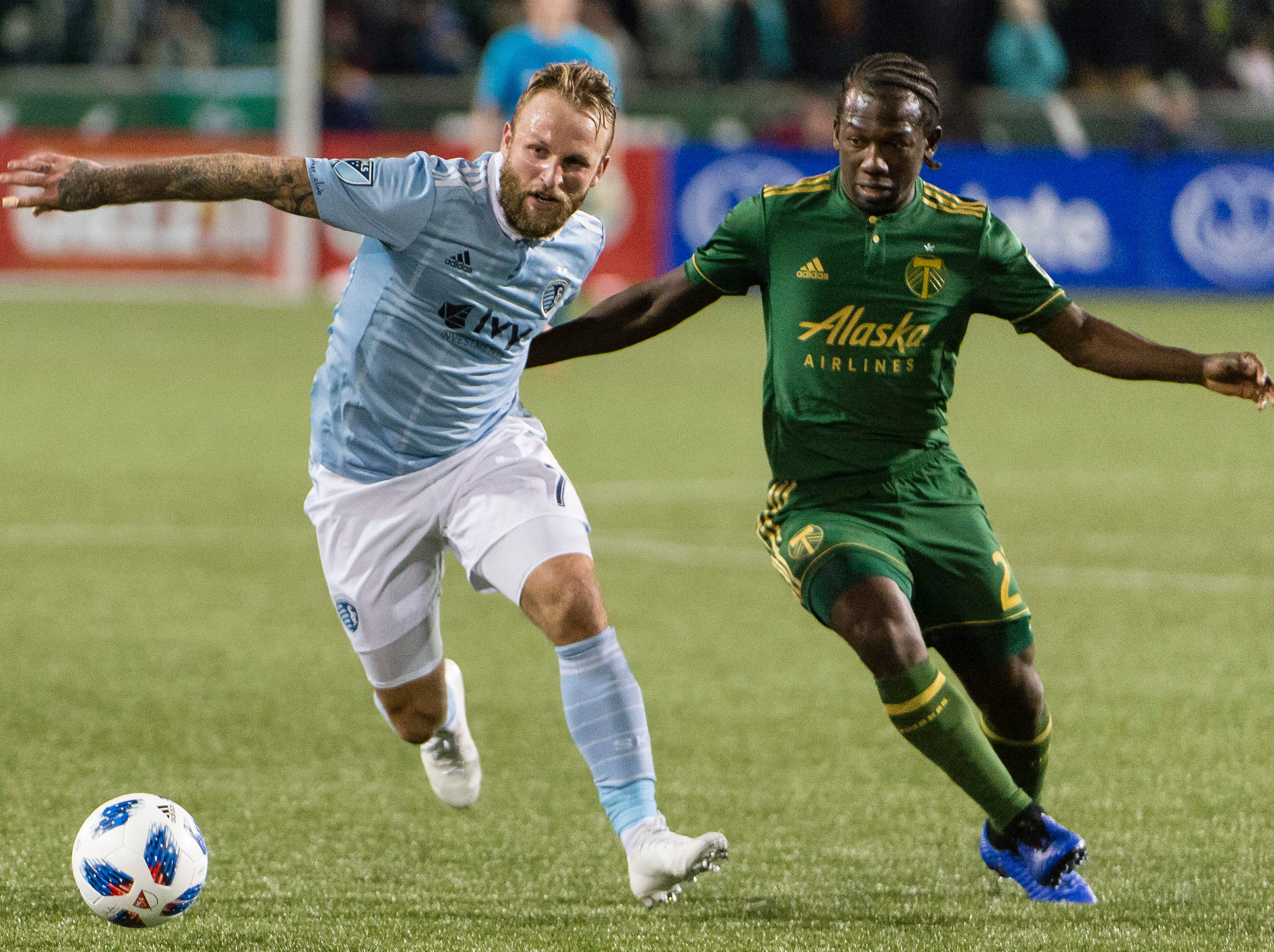 Nov 25, 2018; Portland, OR, USA; Sporting Kansas City forward Johnny Russell (7) controls a pass as he is guarded by Portland Timbers midfielder Diego Chara (21) during the second half in the first leg of the MLS Western Conference Championship at Providence Park. The game ended tied 0-0.  Mandatory Credit: Troy Wayrynen-USA TODAY Sports