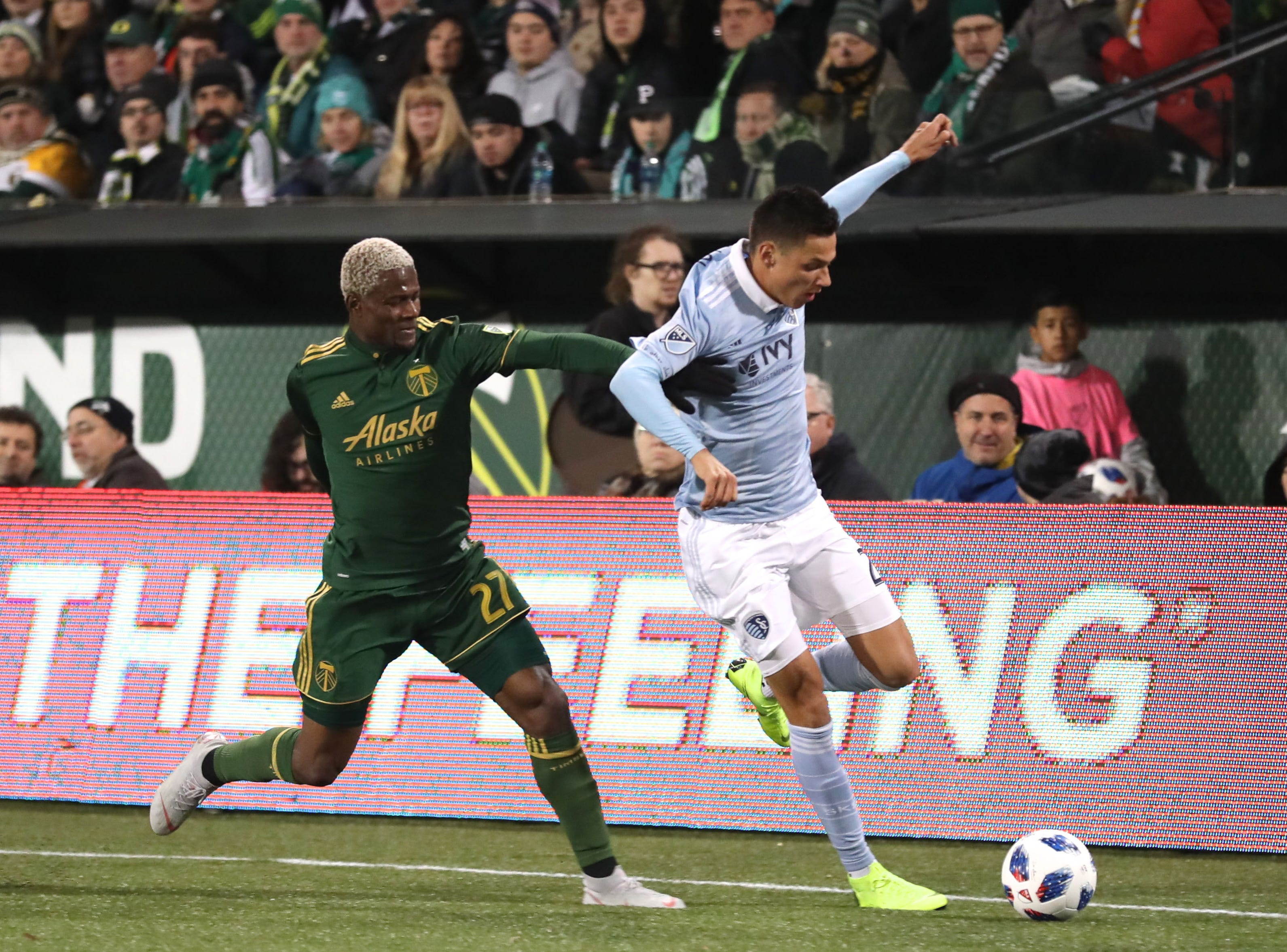 Nov 25, 2018; Portland, OR, USA; Sporting Kansas City forward Daniel Salloi (20) runs by Portland Timbers forward Dairon Asprilla (27) in the first half of the first leg of the MLS Western Conference Championship at Providence Park. Mandatory Credit: Jaime Valdez-USA TODAY Sports