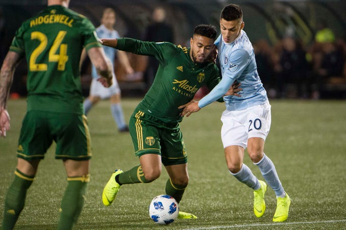 Nov 25, 2018; Portland, OR, USA; Portland Timbers defender Bill Tuiloma (25) is held up by Sporting Kansas City forward Daniel Salloi (20) during the second half in the first leg of the MLS Western Conference Championship at Providence Park. The game ended tied 0-0. Mandatory Credit: Troy Wayrynen-USA TODAY Sports
