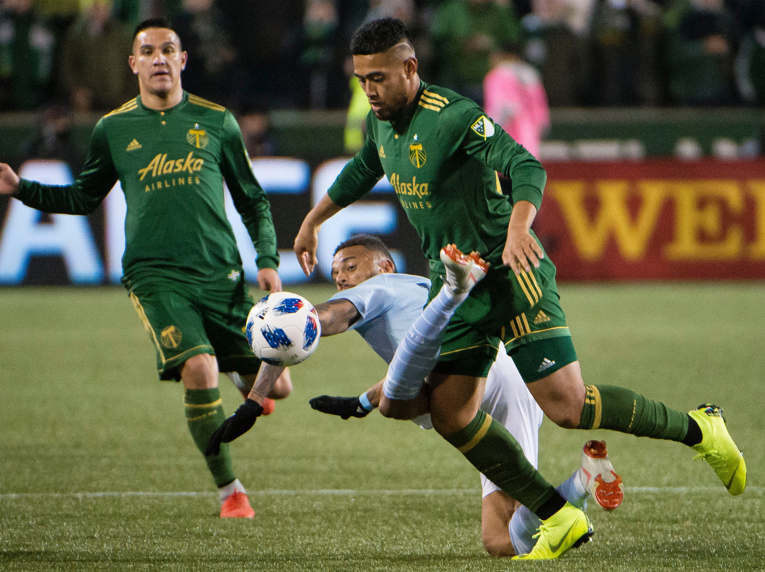 Nov 25, 2018; Portland, OR, USA; Sporting Kansas City forward Khiry Shelton (14) gets tangled up with Portland Timbers defender Bill Tuiloma (25) during the second half in the first leg of the MLS Western Conference Championship at Providence Park. The game ended tied 0-0.  Mandatory Credit: Troy Wayrynen-USA TODAY Sports