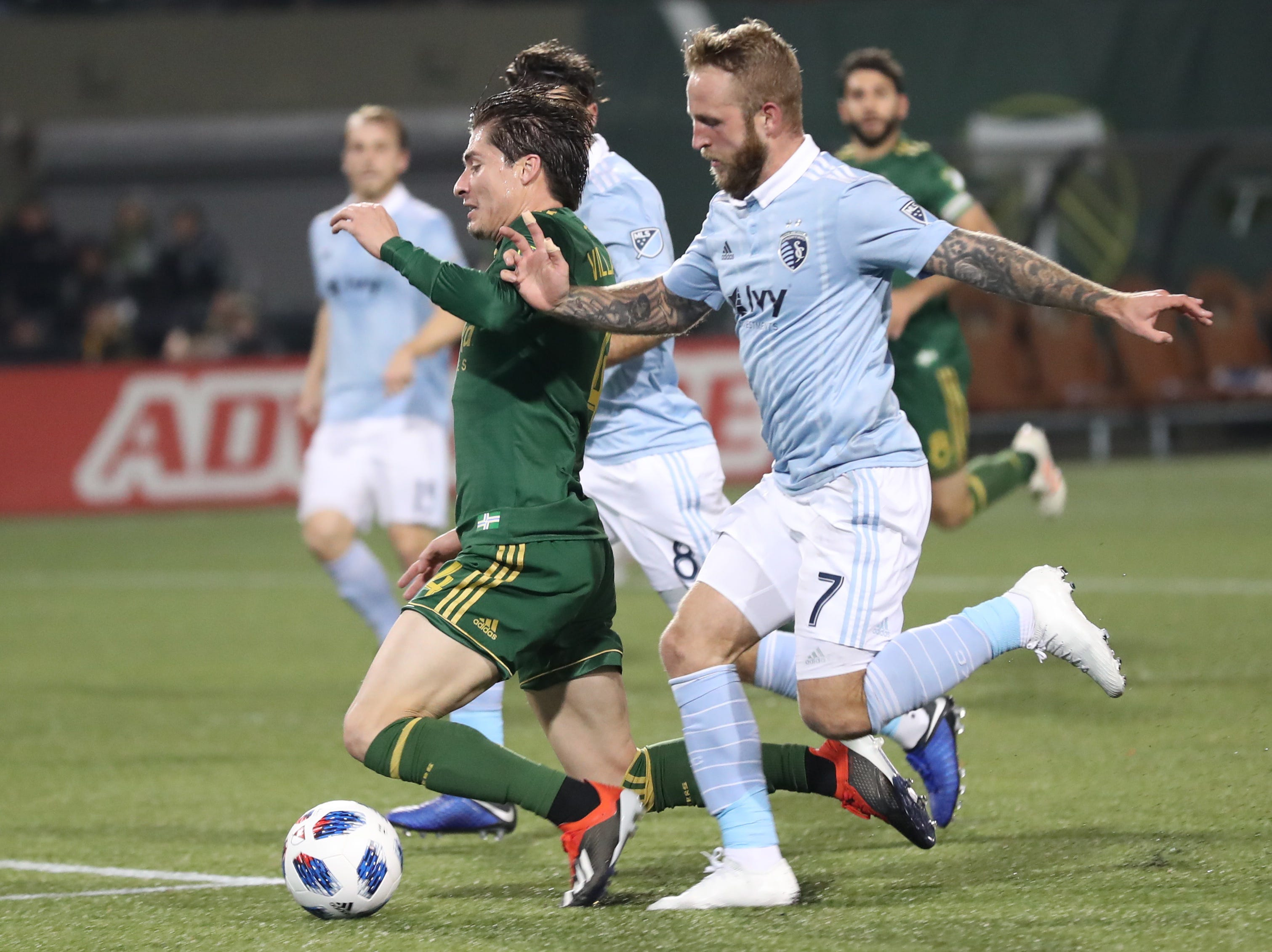 Nov 25, 2018; Portland, OR, USA; The feet of Portland Timbers defender Jorge Villafana (4) and Sporting Kansas City forward Johnny Russell (7) get tangled up in the penalty box in the second of the first leg of the MLS Western Conference Championship at Providence Park. Mandatory Credit: Jaime Valdez-USA TODAY Sports