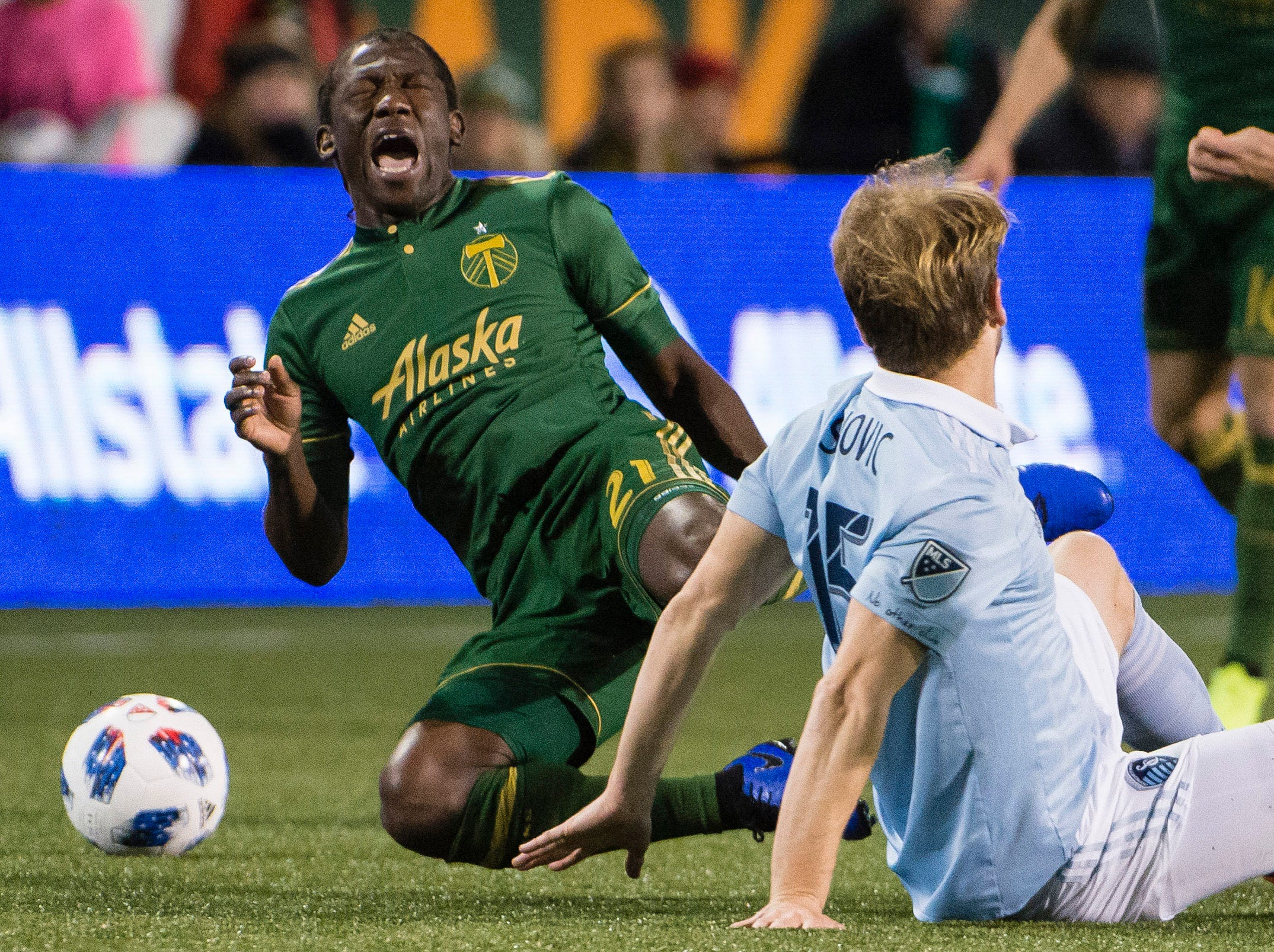 Nov 25, 2018; Portland, OR, USA; Portland Timbers midfielder Diego Chara (21) grimaces in pain after Sporting Kansas City defender Seth Sinovic (15) makes a slide tackle during the first half in the first leg of the MLS Western Conference Championship at Providence Park. The game ended tied 0-0. Mandatory Credit: Troy Wayrynen-USA TODAY Sports