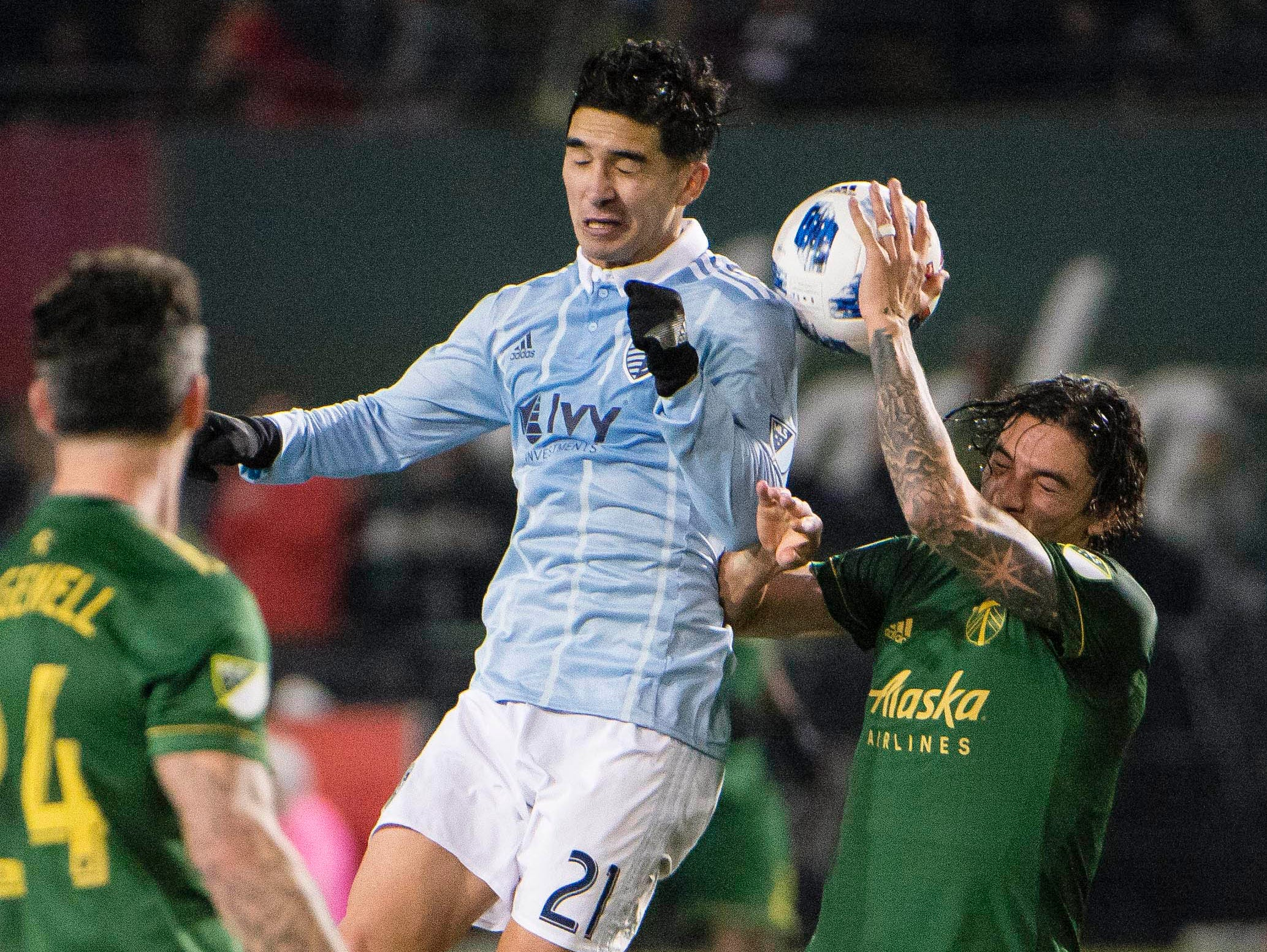Nov 25, 2018; Portland, OR, USA; Sporting Kansas City midfielder Felipe Gutierrez (21) wins a header against Portland Timbers defender Zarek Valentin (16) during the second half in the first leg of the MLS Western Conference Championship at Providence Park. The game ended tied 0-0. Mandatory Credit: Troy Wayrynen-USA TODAY Sports