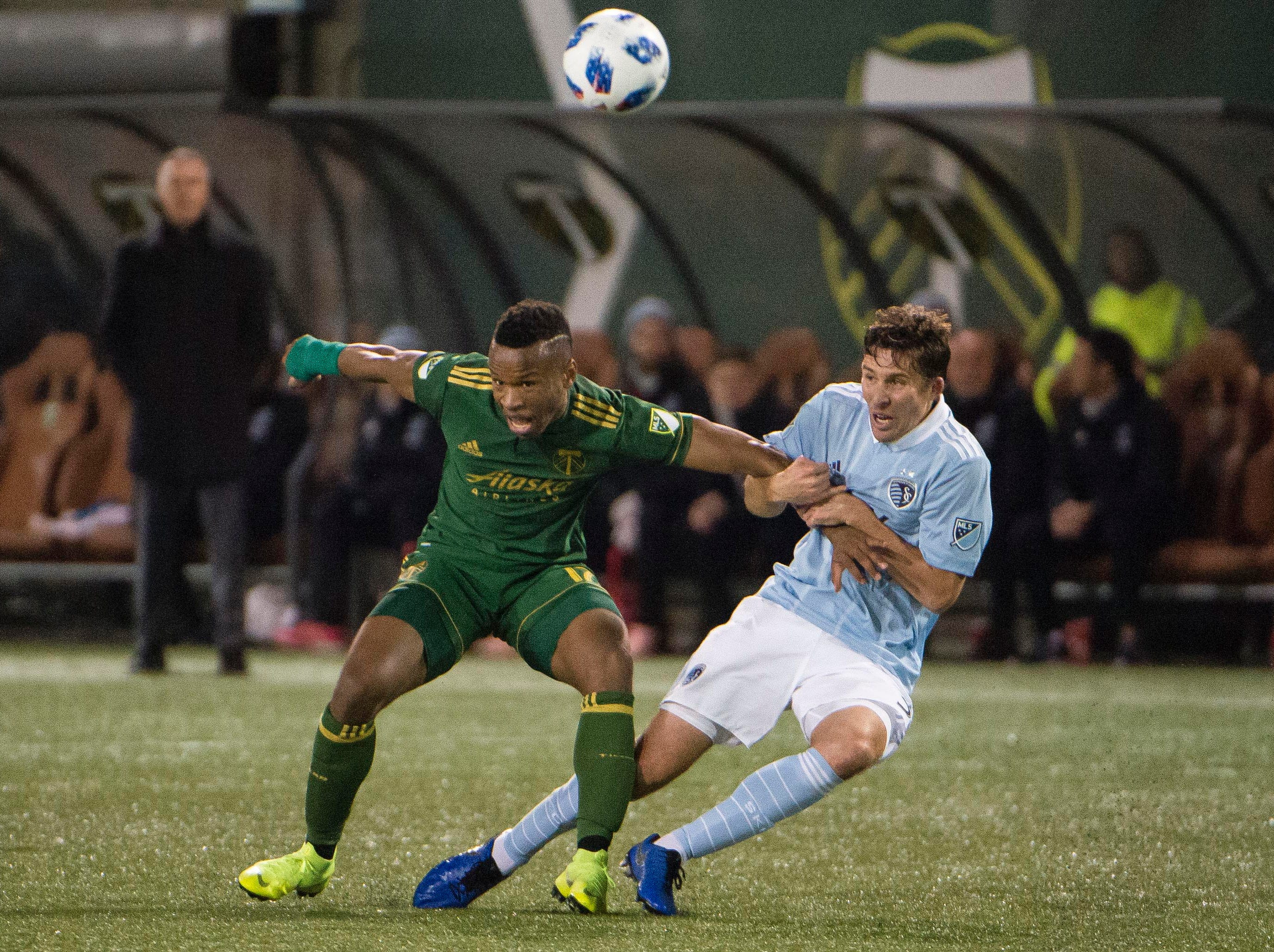 Nov 25, 2018; Portland, OR, USA; Portland Timbers forward Jeremy Ebobisse (17) is held by Sporting Kansas City defender Matt Besler (5) during the second half in the first leg of the MLS Western Conference Championship at Providence Park. The game ended tied 0-0. Mandatory Credit: Troy Wayrynen-USA TODAY Sports