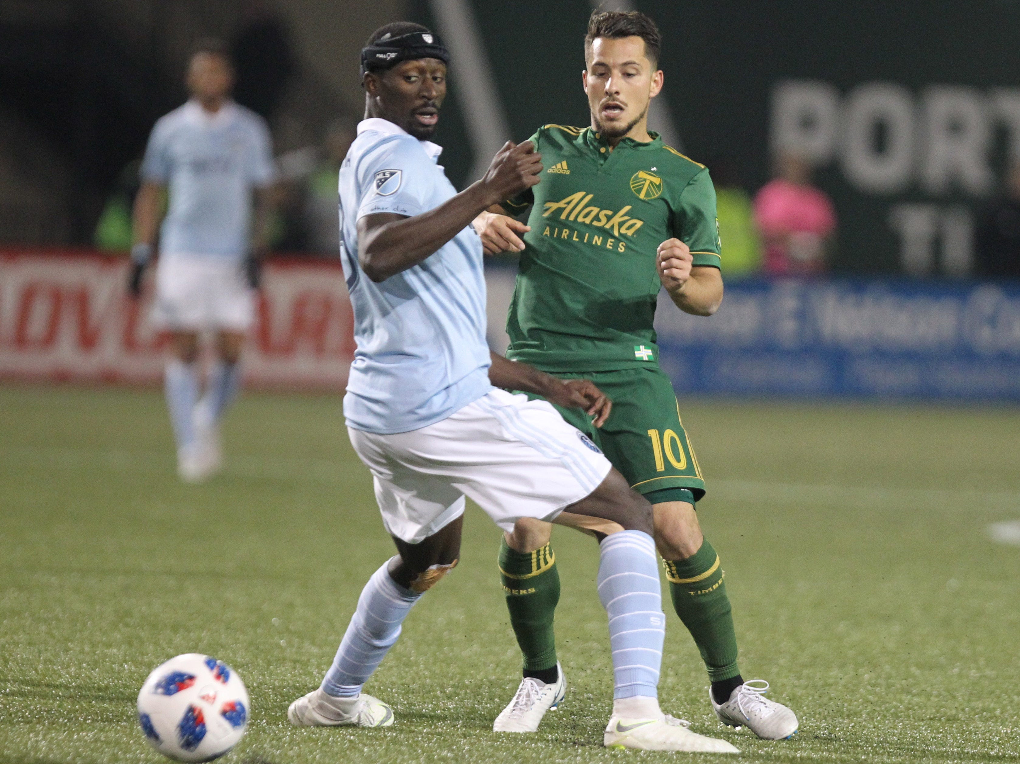 Nov 25, 2018; Portland, OR, USA; Portland Timbers midfielder Sebastian Blanco (10) passes the ball by Sporting Kansas City defender Ike Opara (3) in the second of the first leg of the MLS Western Conference Championship at Providence Park. Mandatory Credit: Jaime Valdez-USA TODAY Sports