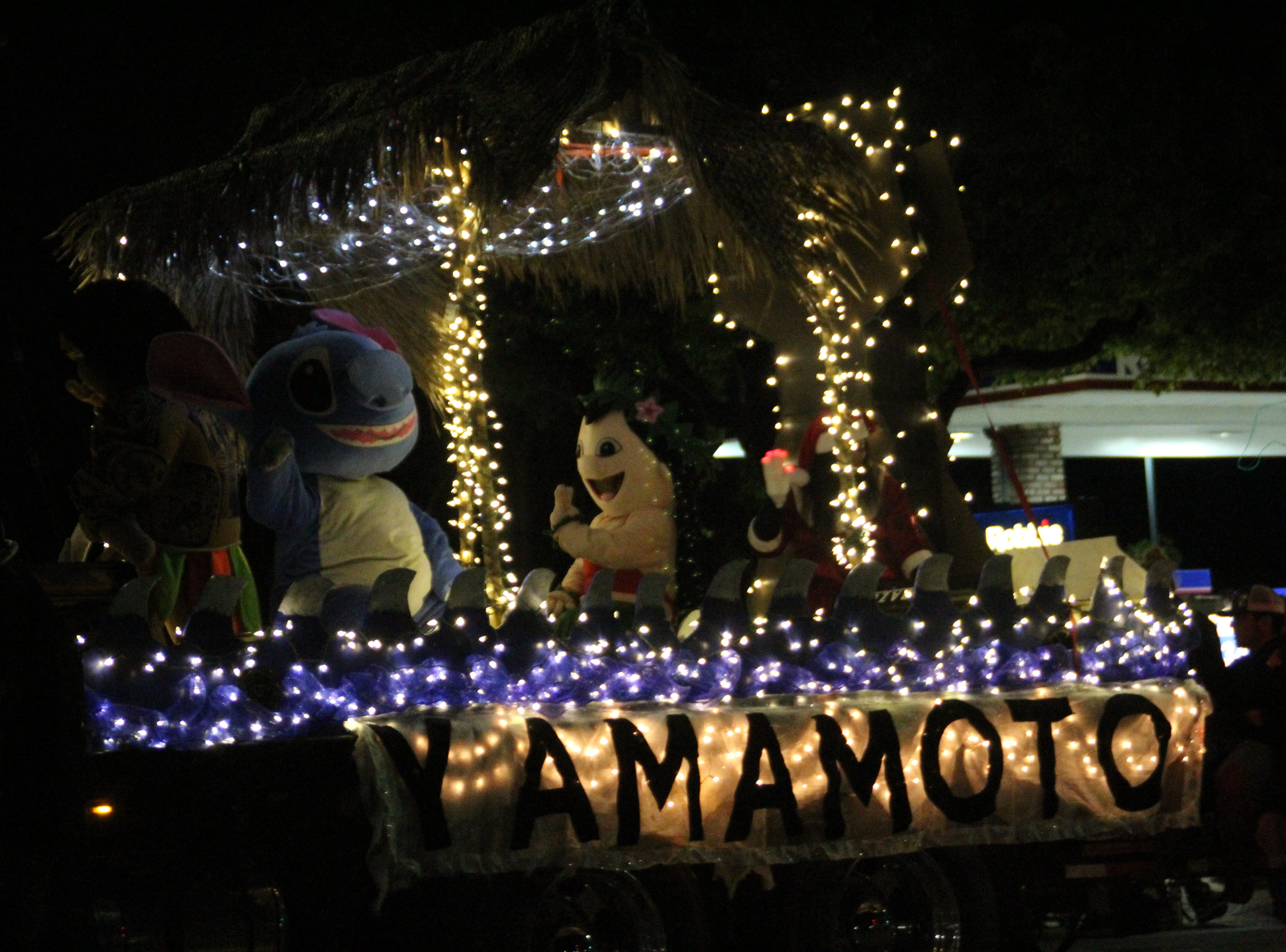"The Disney character ""Stitch"" waves at onlookers on a Hawaiian-themed float at the Salinas Parade of Lights on Sunday."