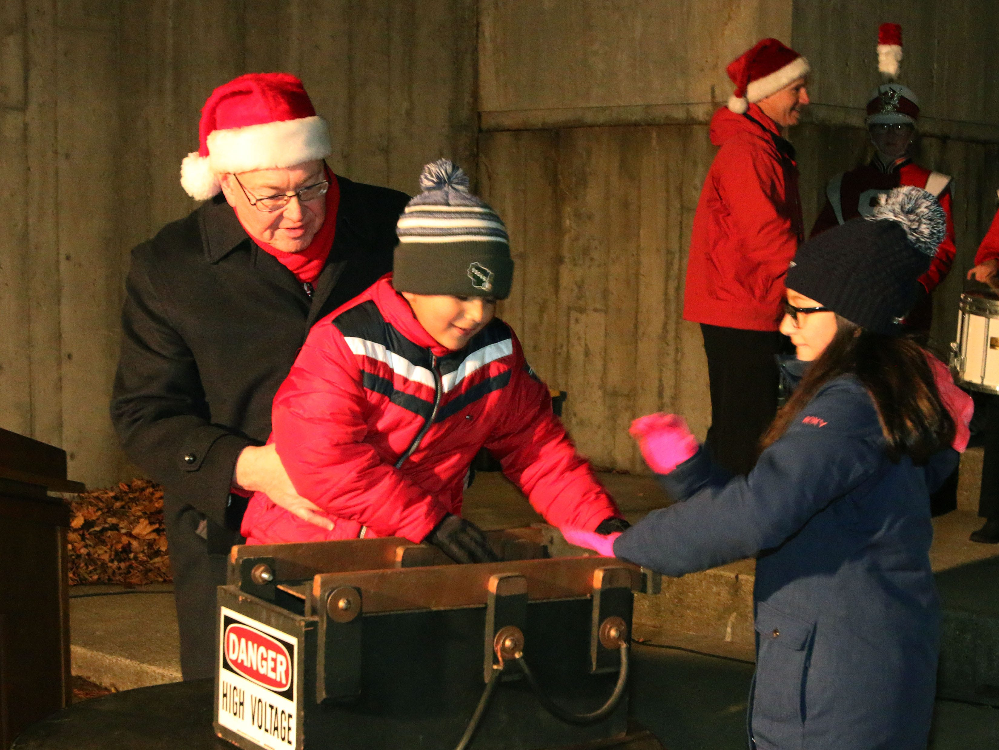 Eli Zamora, 7, center, helps Mayor Michael Vandersteen, left, and Payton Salazar, 11, right, turn on the holiday light display at Mead Library following the 26th Annual Jaycees Holiday Parade, Sunday, November 25, 2018 in Sheboygan, Wis.