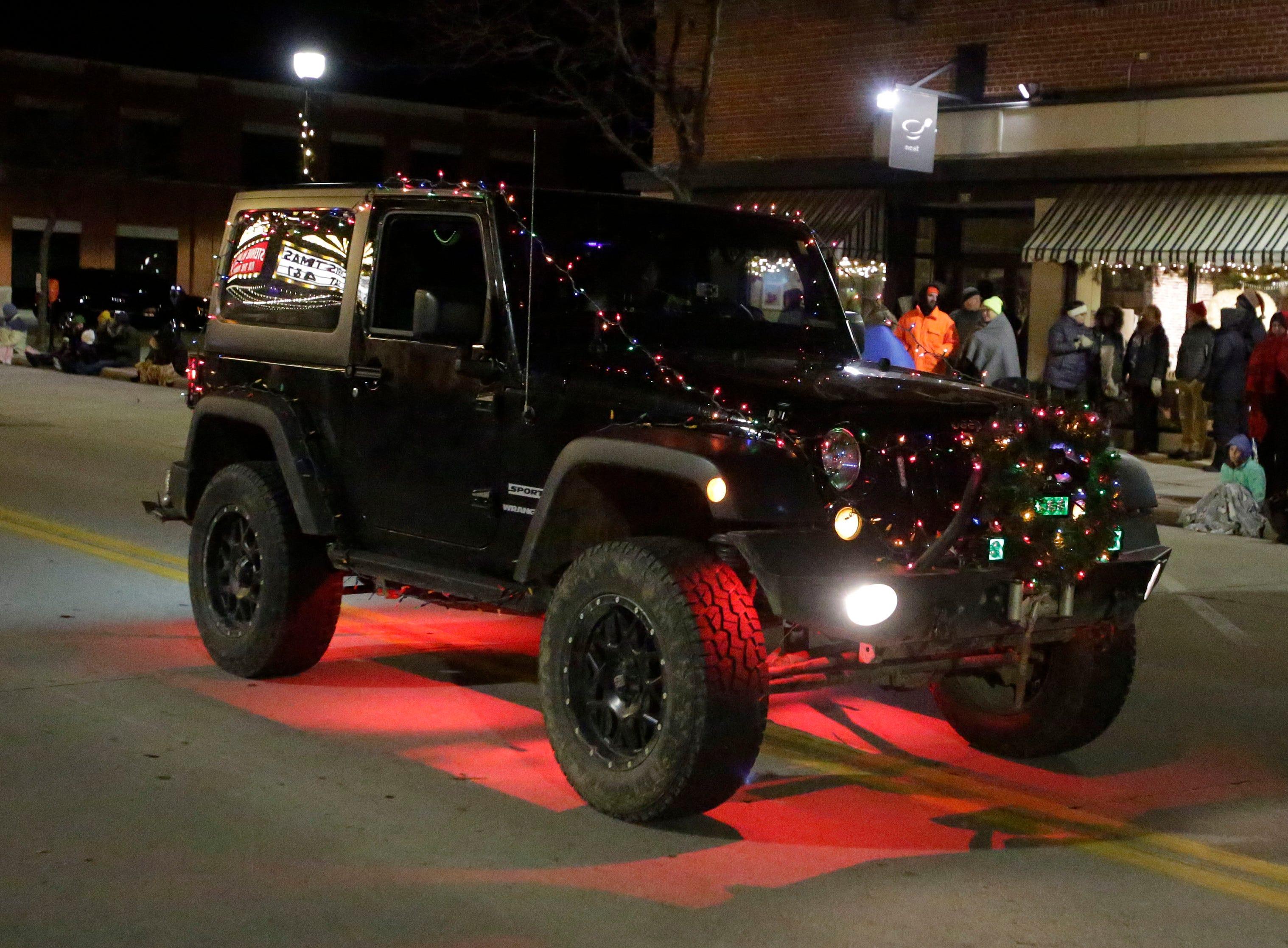 A Jeep glows North 8th Street at the 26th Annual Jaycees Holiday Parade, Sunday, November 25, 2018 in Sheboygan, Wis.