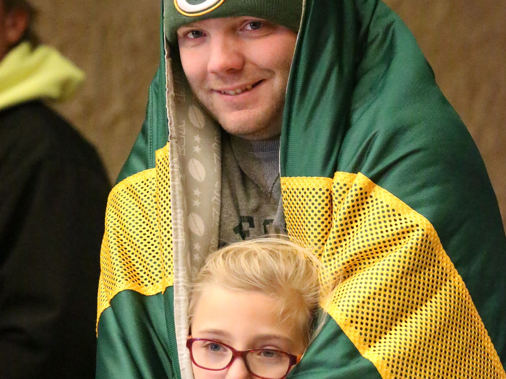 Jeremy Schwarten, of Sheboygan, keeps a blanket wrapped around his daughter Madyson, 8, during the 26th Annual Jaycees Holiday Parade, Sunday, November 25, 2018 in Sheboygan, Wis.