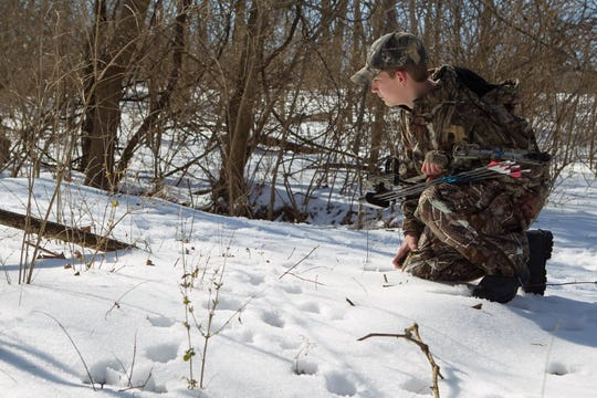 An archer checks deer tracks in the snow.