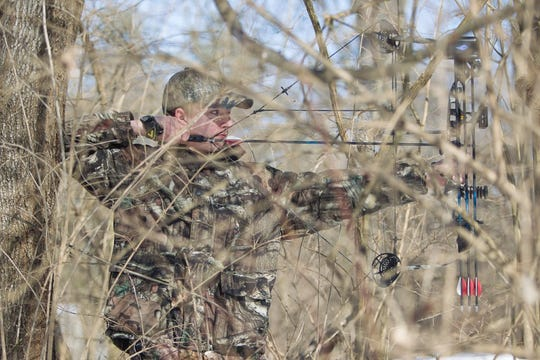 A bowhunter ready to shoot through brush.