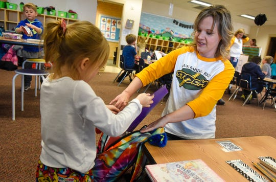 Teacher Laura Tate helps a kindergarten student pack her backpack at Mississippi Heights Elementary School Monday, Nov. 26, in Sauk Rapids.