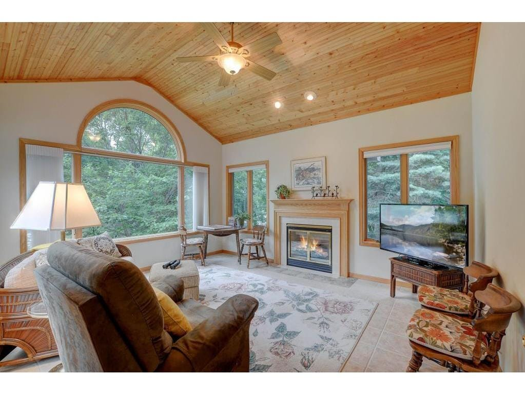 There is a sunroom to provide a quiet sanctuary off the main spacewith a huge bay window, another fireplace and gorgeous wood vaulted ceilings.