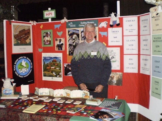 John Davis, the founder of the Alternative Christmas Market at John Wesley United Methodist Church, is shown working a booth at the market.