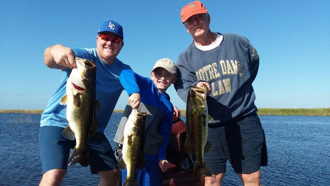 Give thanks for great bass fishing on Lake Okeechobee, said Mac Stuckey of Stuart, right, while fishing with his son-in-law Ben Alderdice and grandson Bennett Alderdice, 7, of Kentucky. They fished Friday with Capt. Nate Shellen of Okeechobeebassfishing.com.