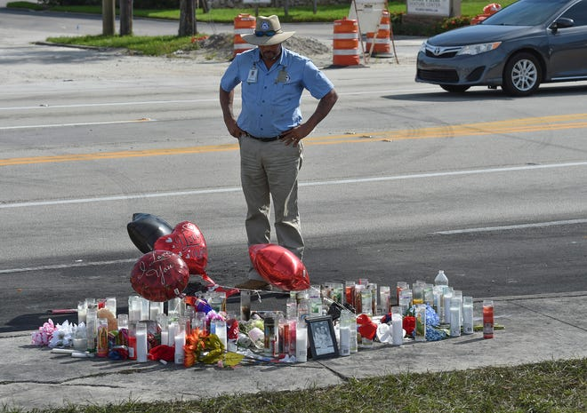 William Brooks Jr., of the Fort Pierce Utilities Authority, stops to view a road-side memorial on Monday, Nov. 26, 2018, at the sight of a three-car fiery crash that that killed five people on Friday, Nov. 23 on South 25th Street, at Midway Road in Fort Pierce. Cars have been stopping at the sight on Monday as people pause and grieve the loss of the victims involved in the crash.