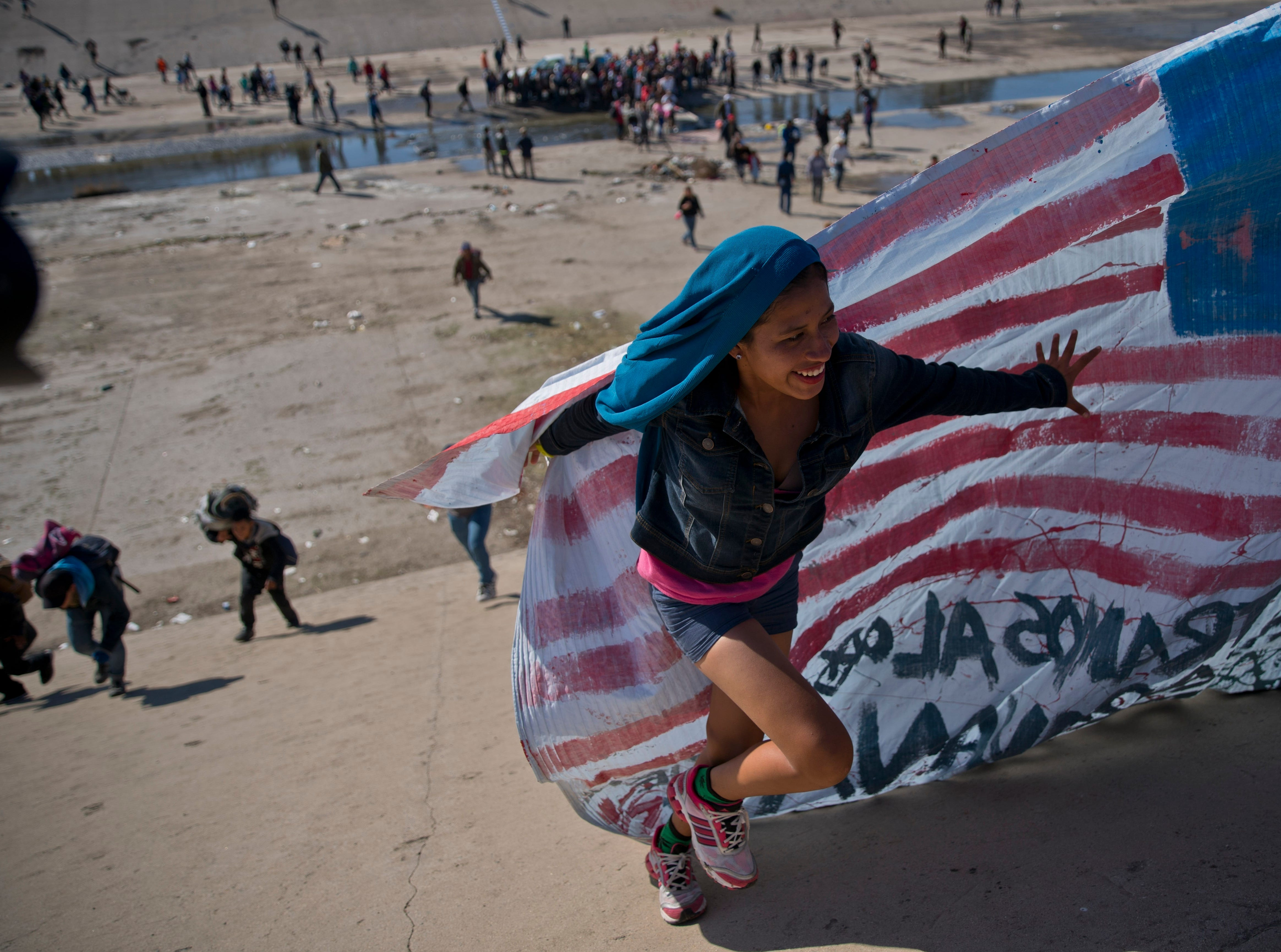 A migrant woman helps carry a handmade U.S. flag up the riverbank at the Mexico-U.S. border after getting past Mexican police at the Chaparral border crossing in Tijuana, Mexico, Sunday, Nov. 25, 2018, as a group of migrants tries to reach the U.S. The mayor of Tijuana has declared a humanitarian crisis in his border city and says that he has asked the United Nations for aid to deal with the approximately 5,000 Central American migrants who have arrived in the city.