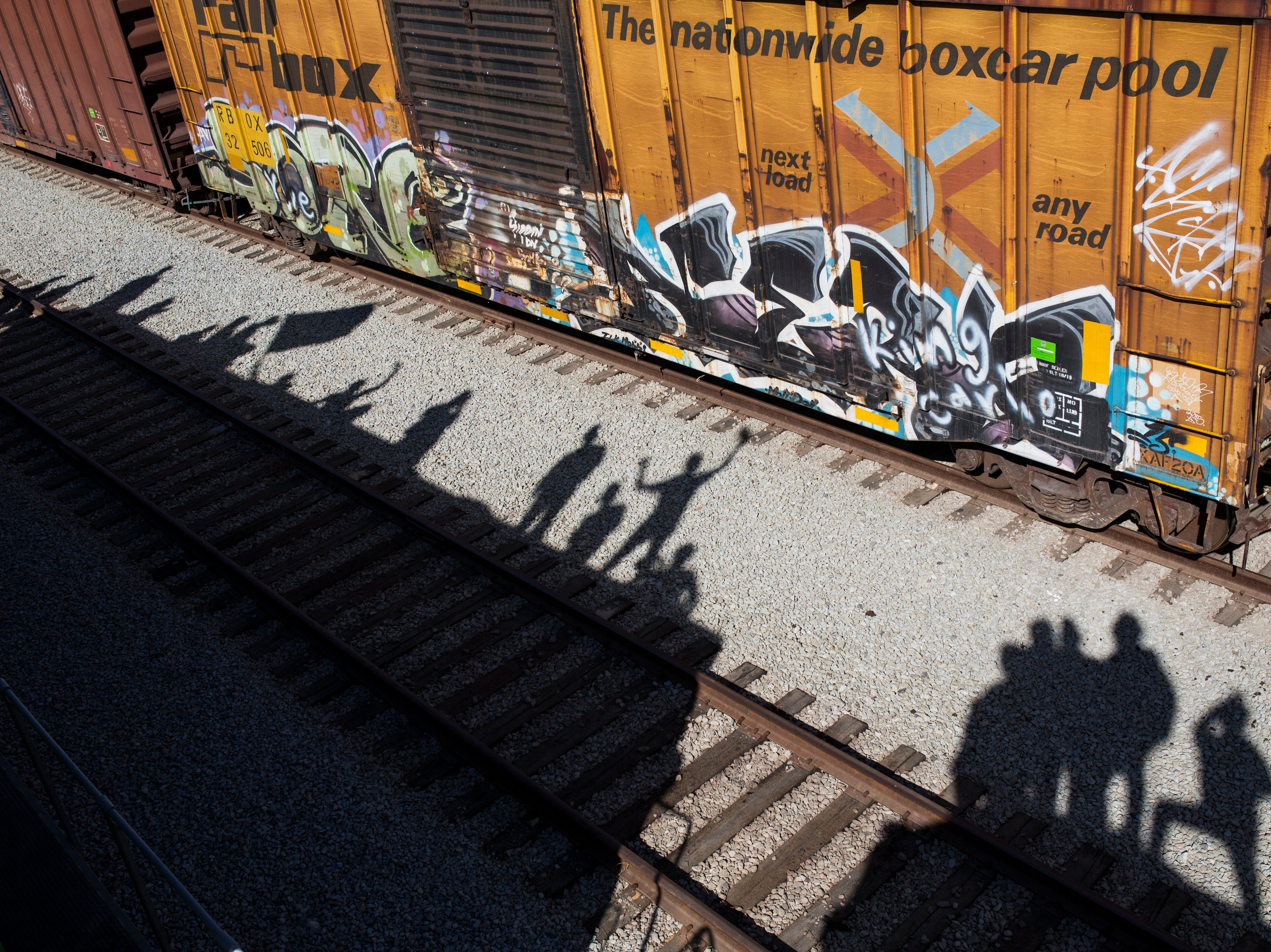 Shadows of migrants are cast on the railroad tracks at the Mexico-U.S. border in Tijuana, Mexico, Sunday, Nov. 25, 2018, as a group of migrants tries to reach the U.S. The mayor of Tijuana has declared a humanitarian crisis in his border city and says that he has asked the United Nations for aid to deal with the approximately 5,000 Central American migrants who have arrived in the city.