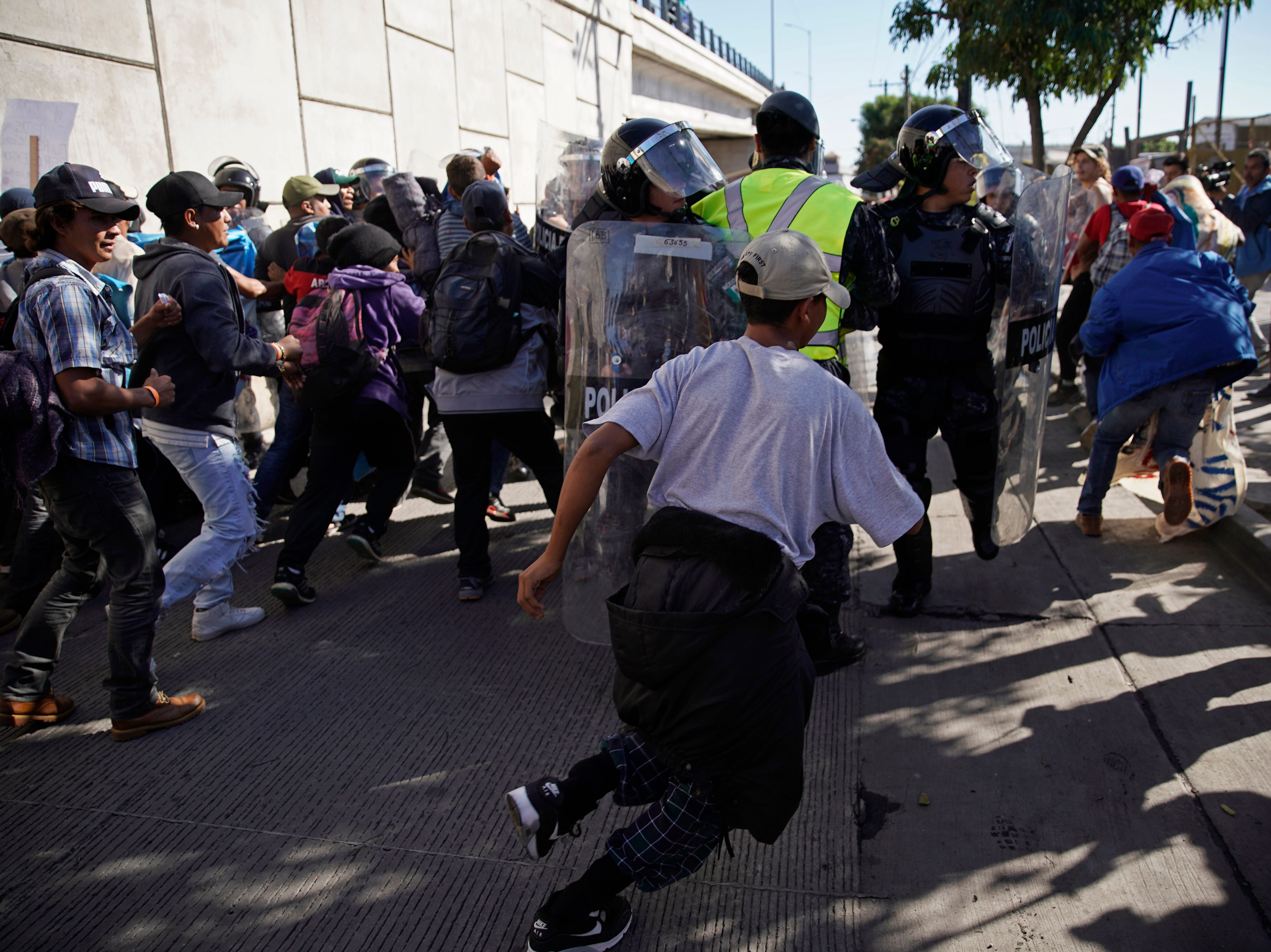 Migrants break past a line of police as they run toward the Chaparral border crossing in Tijuana, Mexico, Sunday, Nov. 25, 2018, near the San Ysidro entry point into the U.S. More than 5,000 migrants are camped in and around a sports complex in Tijuana after making their way through Mexico in recent weeks via caravan.