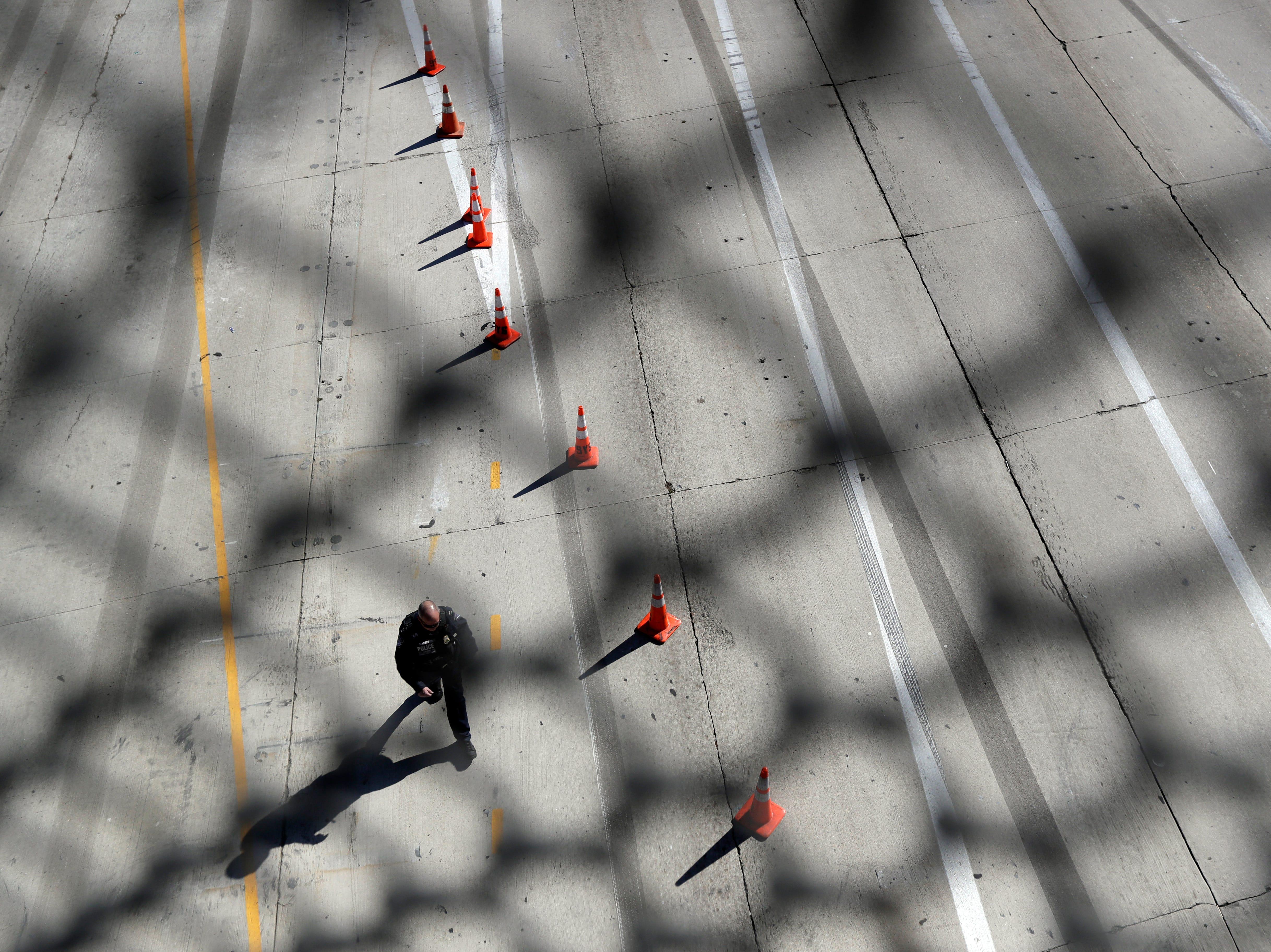 An official walks along the empty lanes of Interstate 5, where it reaches the San Ysidro port of entry, after closing the port Sunday, Nov. 25, 2018, in San Diego. Migrants approaching the U.S. border from Mexico were enveloped with tear gas Sunday after a few tried to breach the fence separating the two countries.