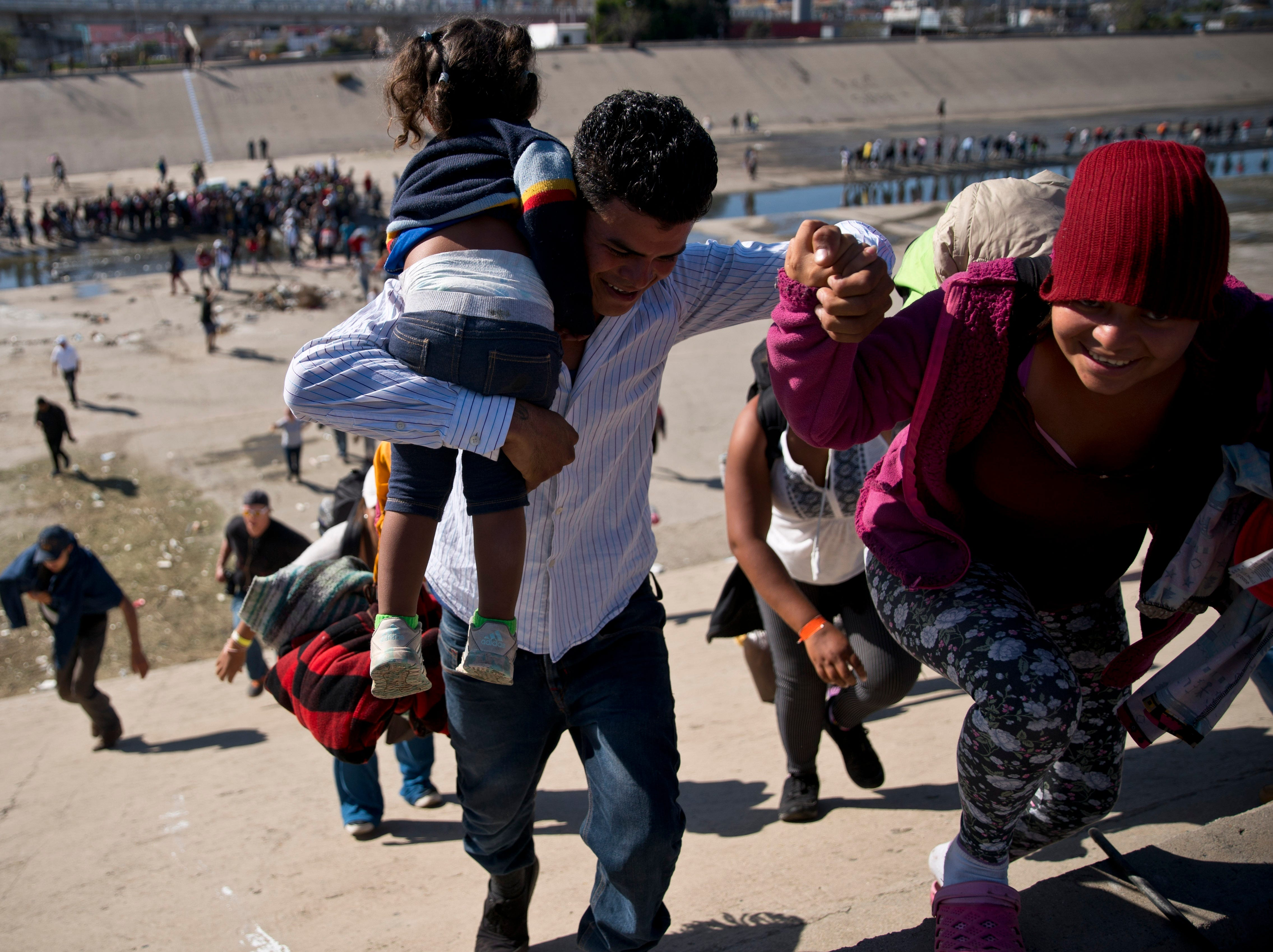 Migrants walk up a riverbank at the Mexico-U.S. border after getting past a line of Mexican police at the Chaparral border crossing in Tijuana, Mexico, Sunday, Nov. 25, 2018, as they try to reach the U.S. The mayor of Tijuana has declared a humanitarian crisis in his border city and says that he has asked the United Nations for aid to deal with the approximately 5,000 Central American migrants who have arrived in the city.