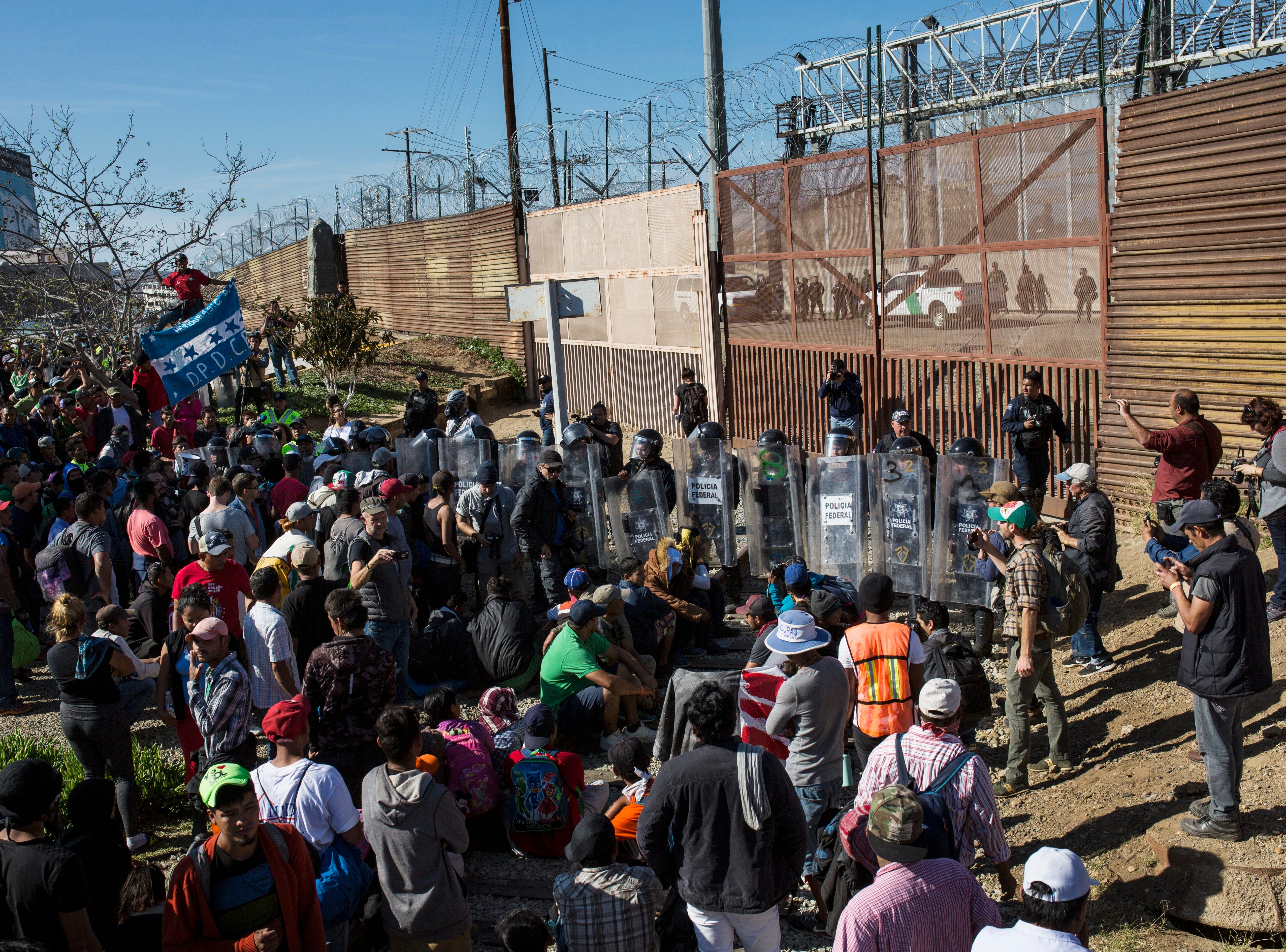 Migrants stand at the Mexico-U.S. border wall where Mexican federal police stand guard at the Chaparral crossing in Tijuana, Mexico, Sunday, Nov. 25, 2018, as they try to reach the U.S. The mayor of Tijuana has declared a humanitarian crisis in his border city and says that he has asked the United Nations for aid to deal with the approximately 5,000 Central American migrants who have arrived in the city.