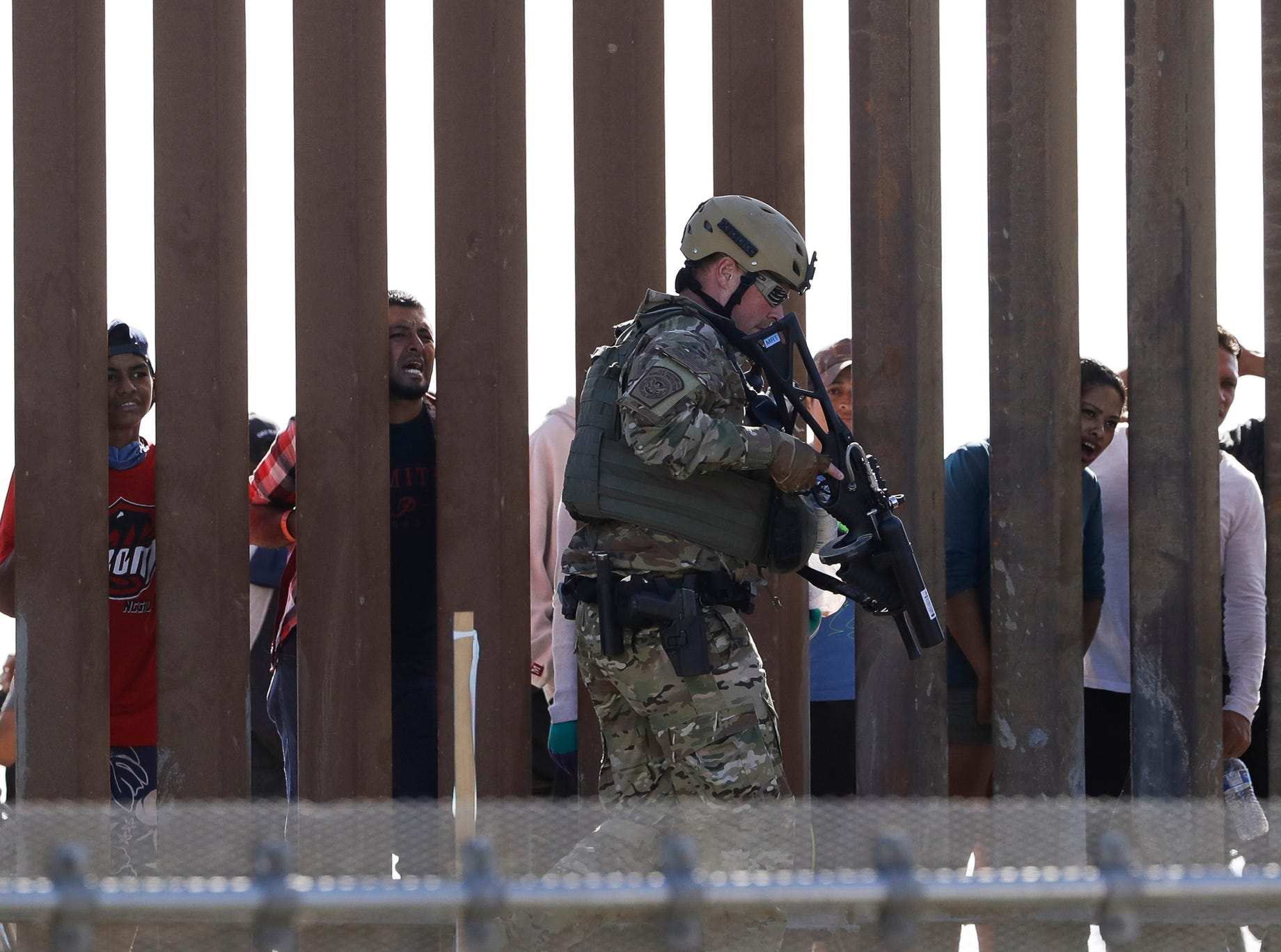 U.S. Customs and Border Protection officers walks along a wall at the border between Mexico and the United States, as seen from San Diego on Sunday, Nov. 25, 2018. Migrants approaching the U.S. border from Mexico were enveloped with tear gas Sunday after a few tried to breach a fence separating the two countries. The Border Patrol office in San Diego said via Twitter that pedestrian crossings have been suspended at the San Ysidro port of entry at both the East and West facilities. All northbound and southbound traffic was halted.