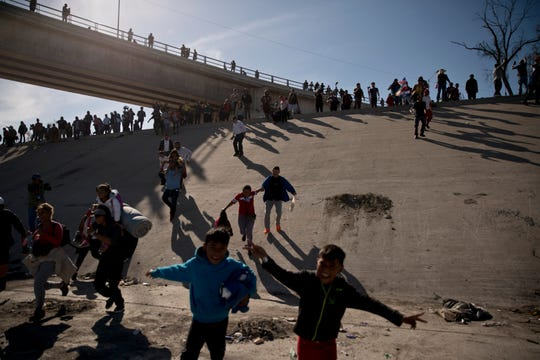 Migrants cross the river at the Mexico-U.S. border after pushing past a line of Mexican police at the Chaparral crossing in Tijuana, Mexico, Sunday, Nov. 25, 2018, as they try to reach the U.S.  The mayor of Tijuana has declared a humanitarian crisis in his border city and says that he has asked the United Nations for aid to deal with the approximately 5,000 Central American migrants who have arrived in the city.