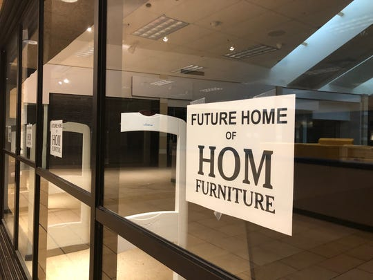 Signs hanging on the former Younkers building tell holiday shoppers that HOM Furniture is coming soon.