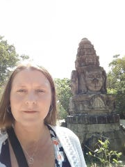 Teacher Amy Bohman stands in front of a piece of historic sculpture in Phnom Penh that is common in Cambodia.